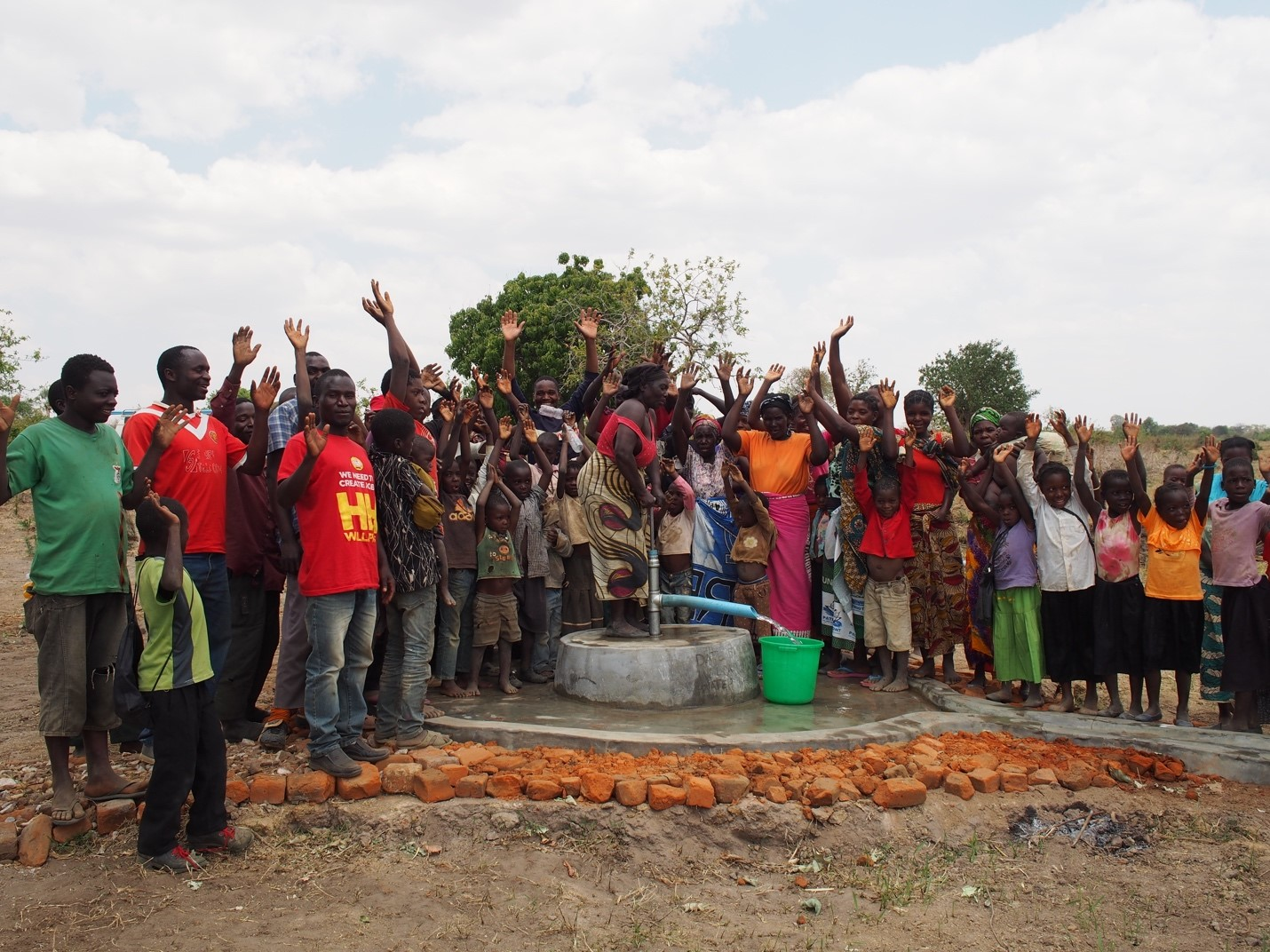 A community celebrates the gift of a clean, safe water supply that a shallow well provides.