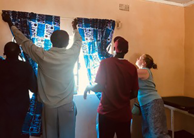 Patricia Clark helps CCAP Heath Department Coordinator Richard Willima hang curtains in the new Egichikeni Mother Care Shelter.