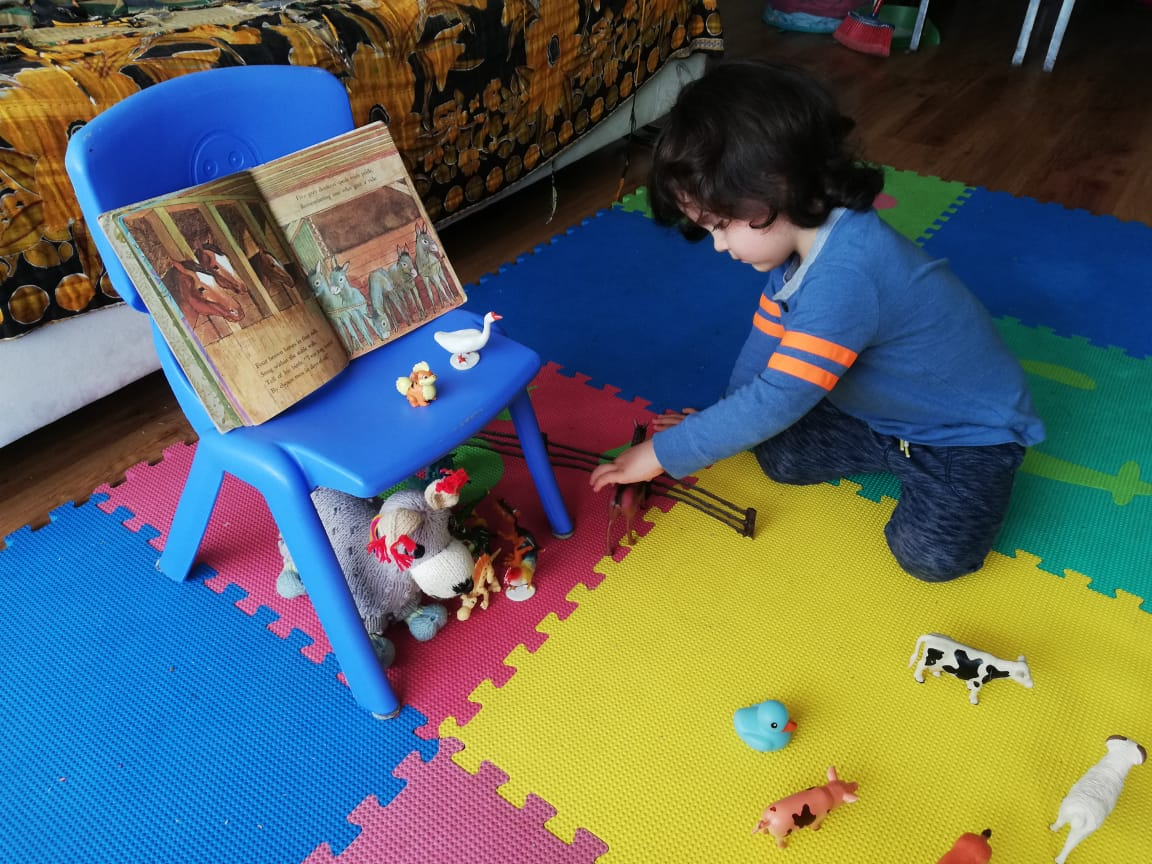 Leandro places the animals while we read 'The Animals' Christmas Eve'