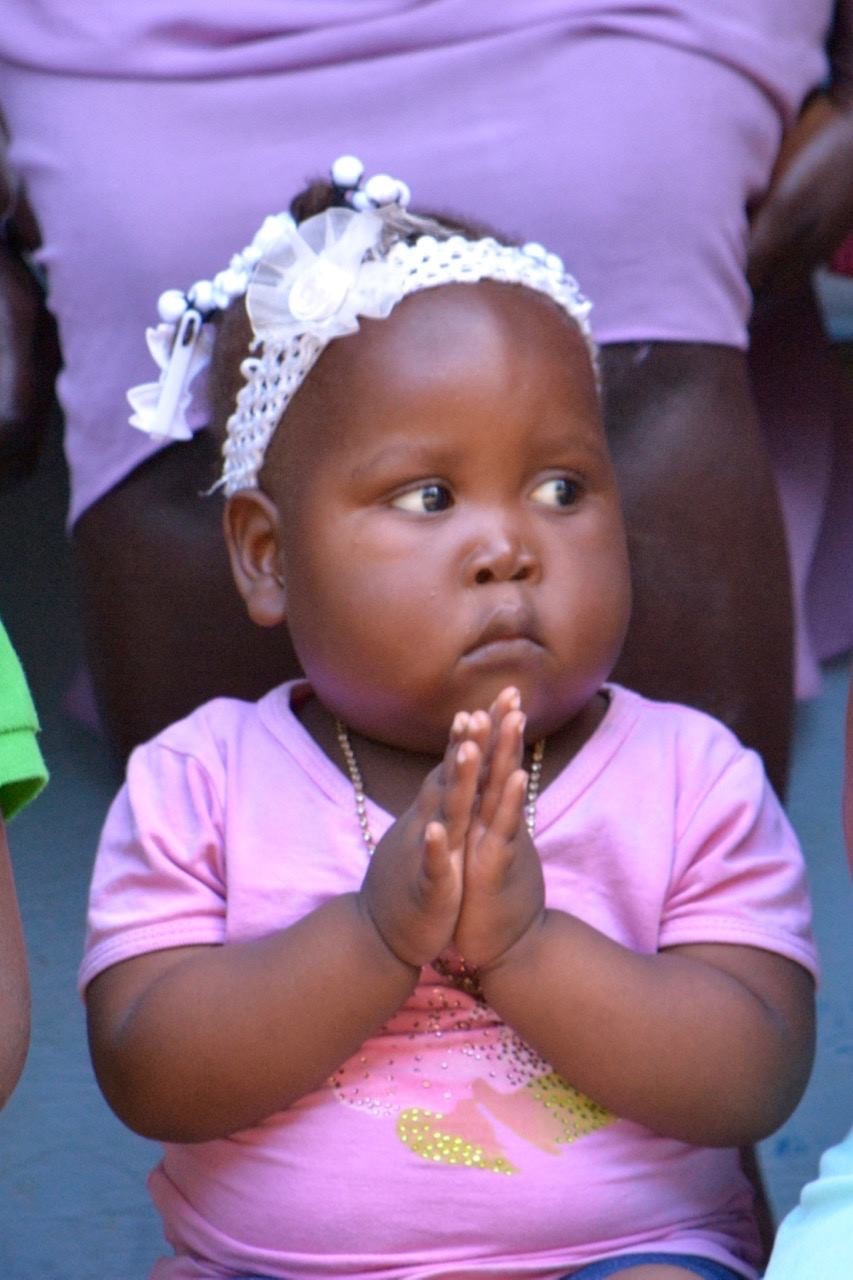A little girl holds her hands in prayer at an event in Port-de-Paix, Haiti. Please continue praying for the people of Haiti.   (Photo by Cindy Corell)