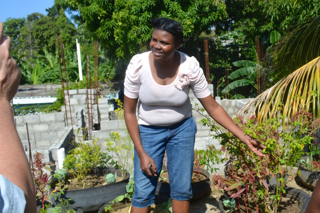 In this February 2016 file photo, a member of a FONDAMA organization in Port-de-Paix talks about the tire gardens she has planted at her home. As Haiti's economic situation threatens famine across the country, FONDAMA is raising funds to help other families create similar gardens to produce food close to home. (Photo: Cindy Corell)