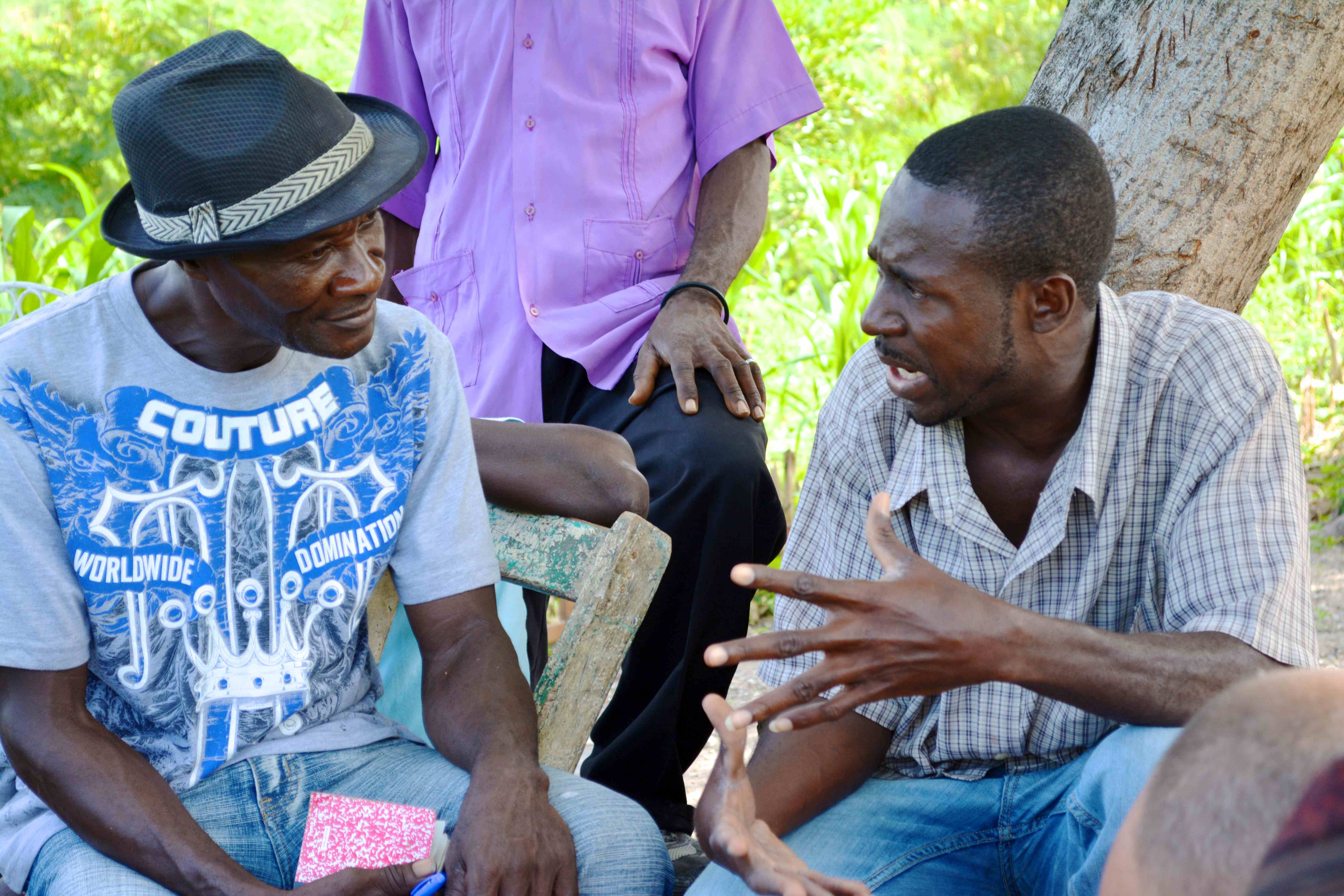 Herve Delisma, right, explains the techniques of using old tires to create gardens in a community near Bayonnais, Haiti, in November 2014. Photo by Cindy Corell.