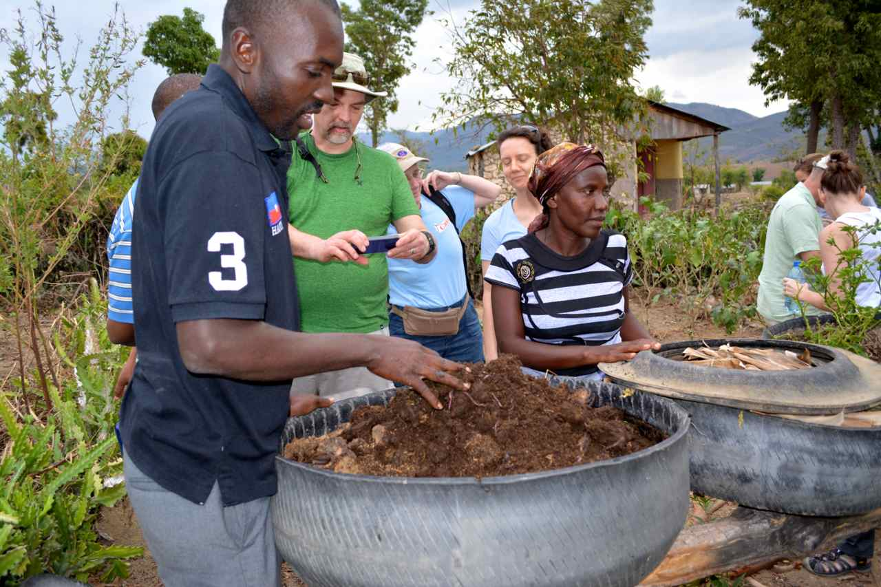 Viljean Louis, coordinator of the Peasants Movement of Bayonnais, explains the advantages of using red worms in yard gardens to help aerate the soil. Photo taken in February 2015. Photo by Cindy Corell.