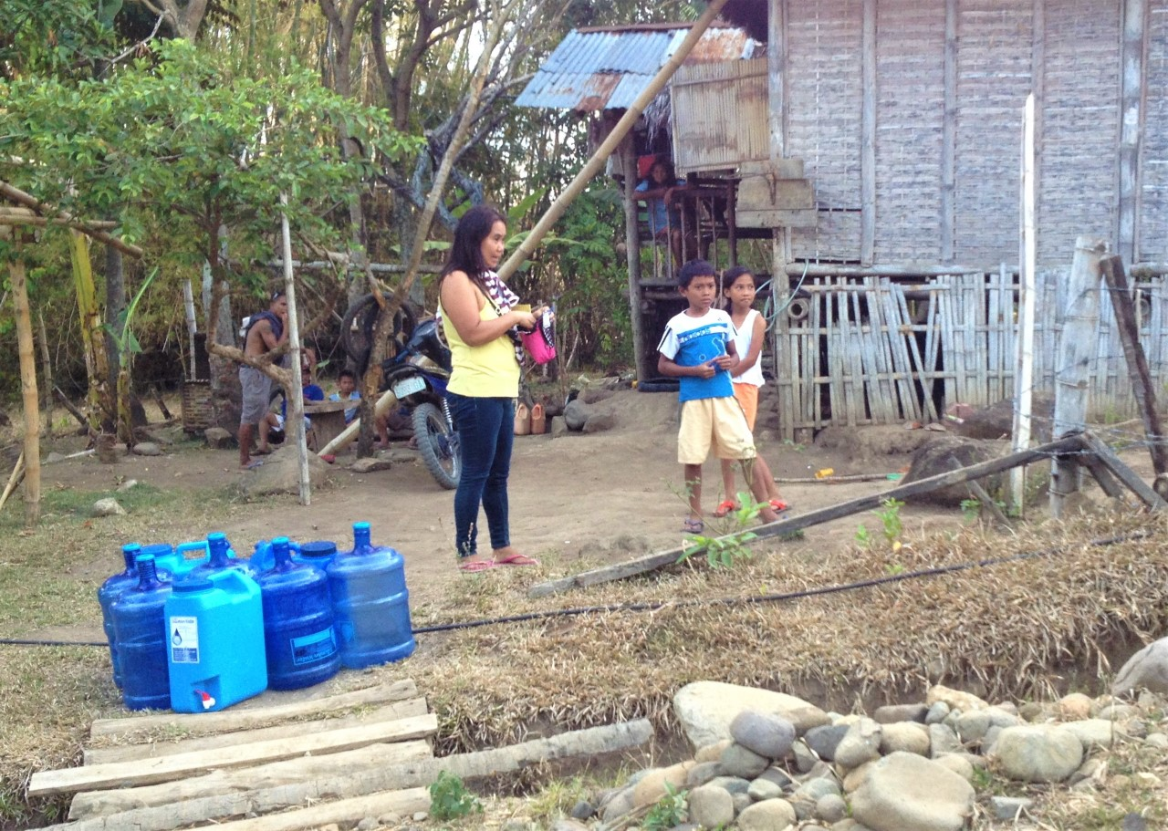 A family receiving clean drinking water from Silliman Water Ministry in Balili, Negros Oriental. (Photos all by permission of subjects and photographer: Cobbie Palm.)