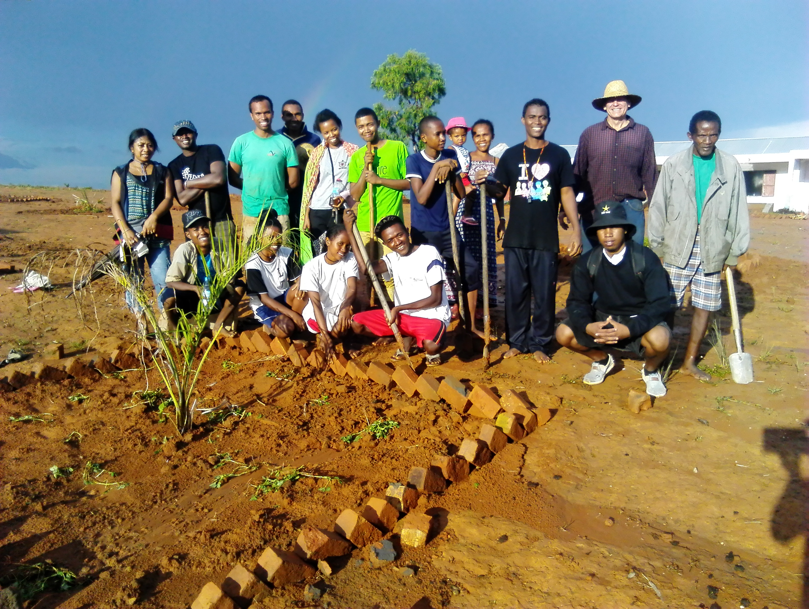Planting trees at Mahatsinjo high school. Caption: Planting trees at the Mahatsinjo public high school. After the rain, a rainbow. Mayor of Mahatsinjo is on right. The principal is holding her child.