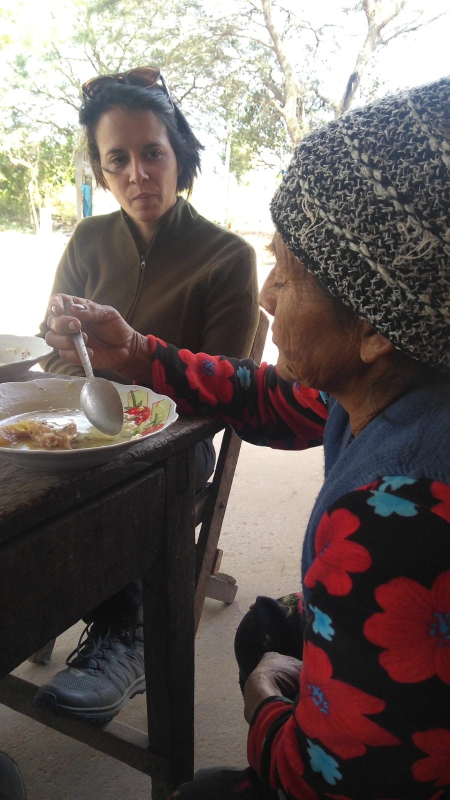 Doña Lindaura shares her story with CWS program officer Agustina Ramos.