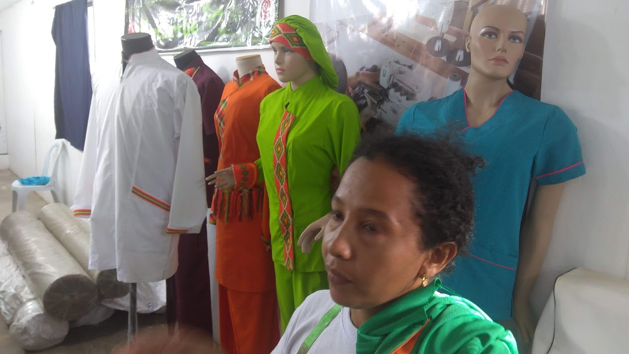 An ex-FARC guerrilla displays fashion designs at their sewing cooperative.