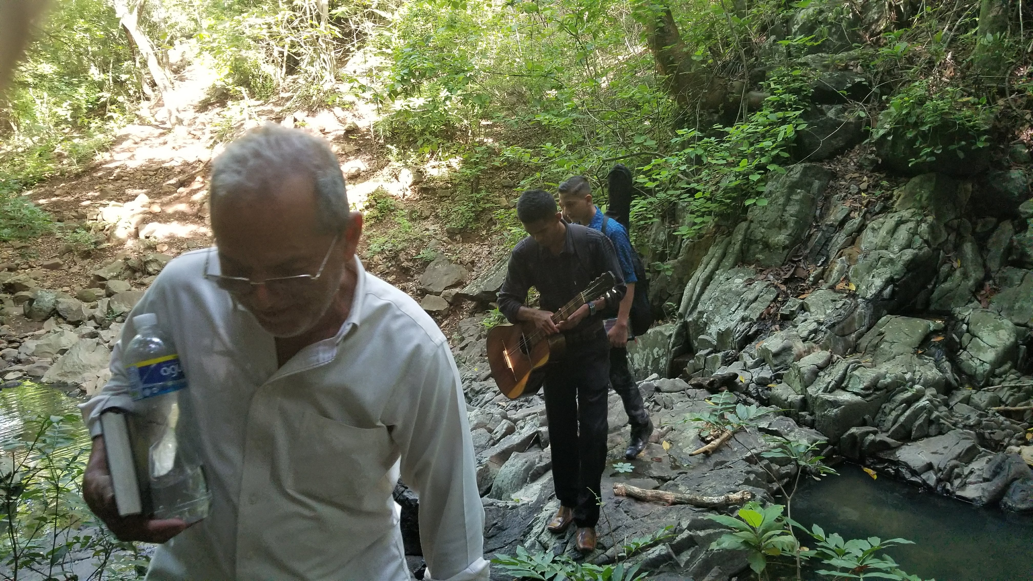 Pastor Juan Rodas and musicians from southern coastal church climb a creek bed to attend a baptism.