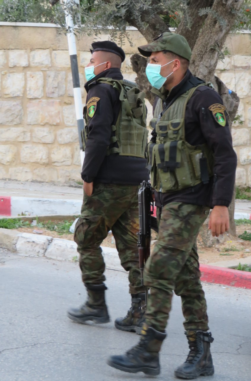 Palestinian security forces, donning masks, outside of the Angel Hotel in Beit Jala.