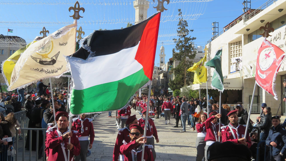 Bethlehem celebrated Christmas Eve under a clear blue sky and with Palestinian flags and scout troops.