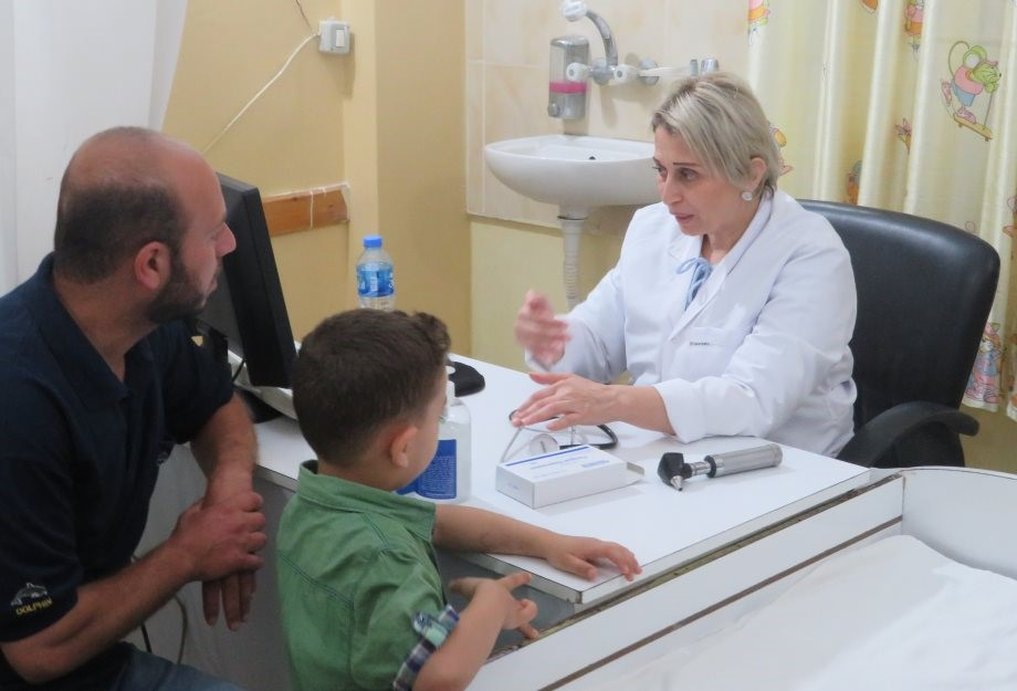 A father with his young son consults the doctor at the Family Health Center in the Darraj area of Gaza.