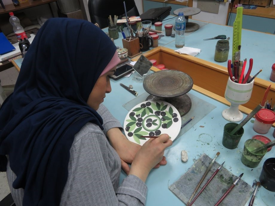 A young artist painting one of the many ceramic items available for purchase at the Atfaluna Society for Deaf Children.