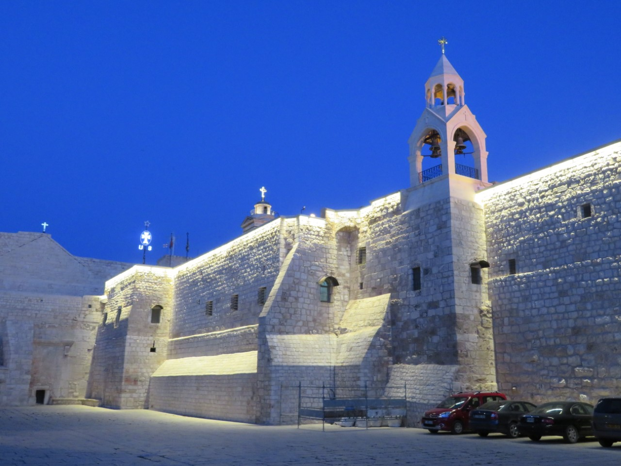 The Church of the Nativity in Bethlehem stands empty against a blue sky, just after dusk.  Tourism has come to a complete standstill due to the Coronavirus pandemic.