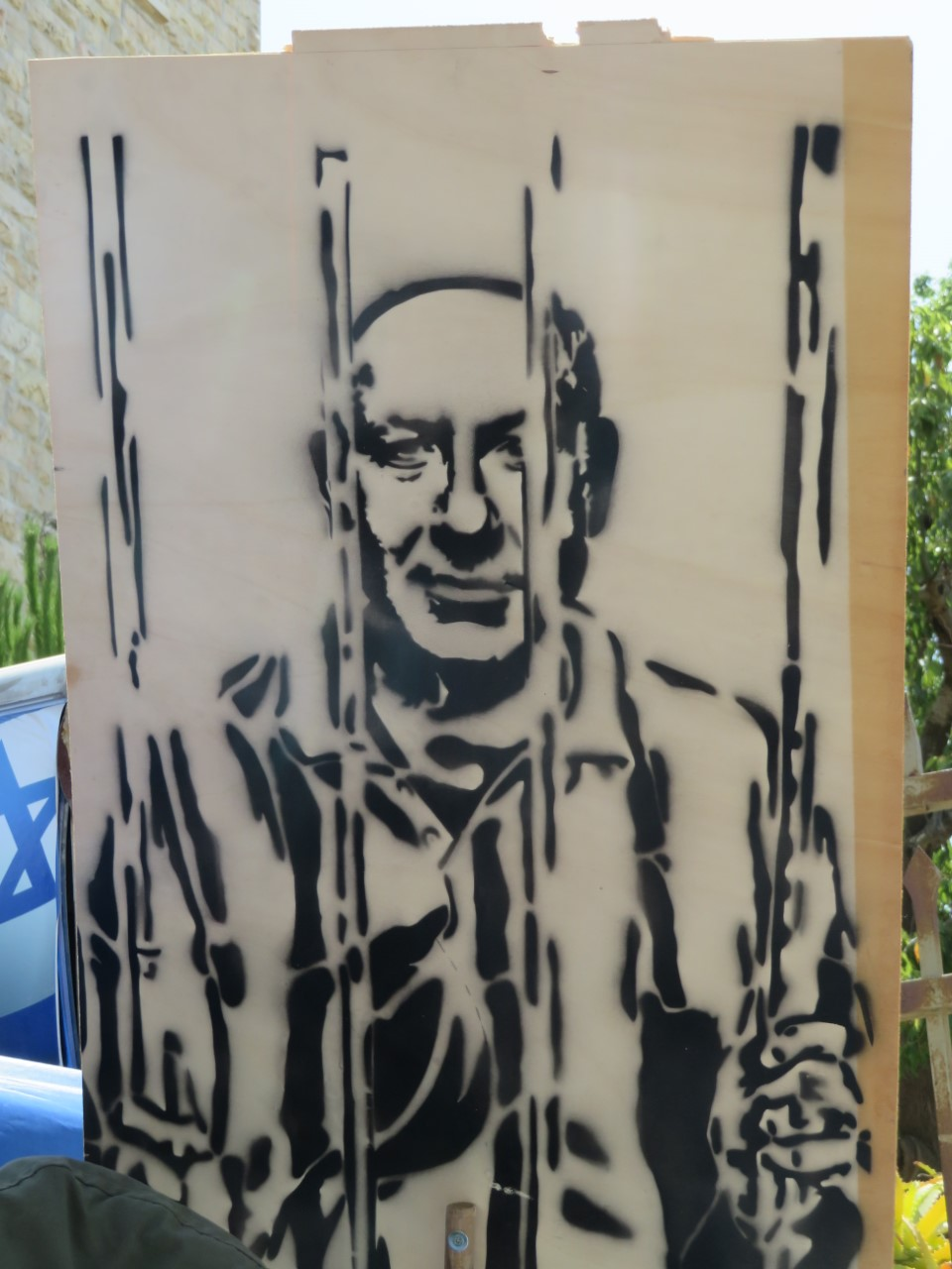 A protest sign outside of the Prime Minister's residence in Jerusalem, depicting Benjamin Netanyahu behind bars.