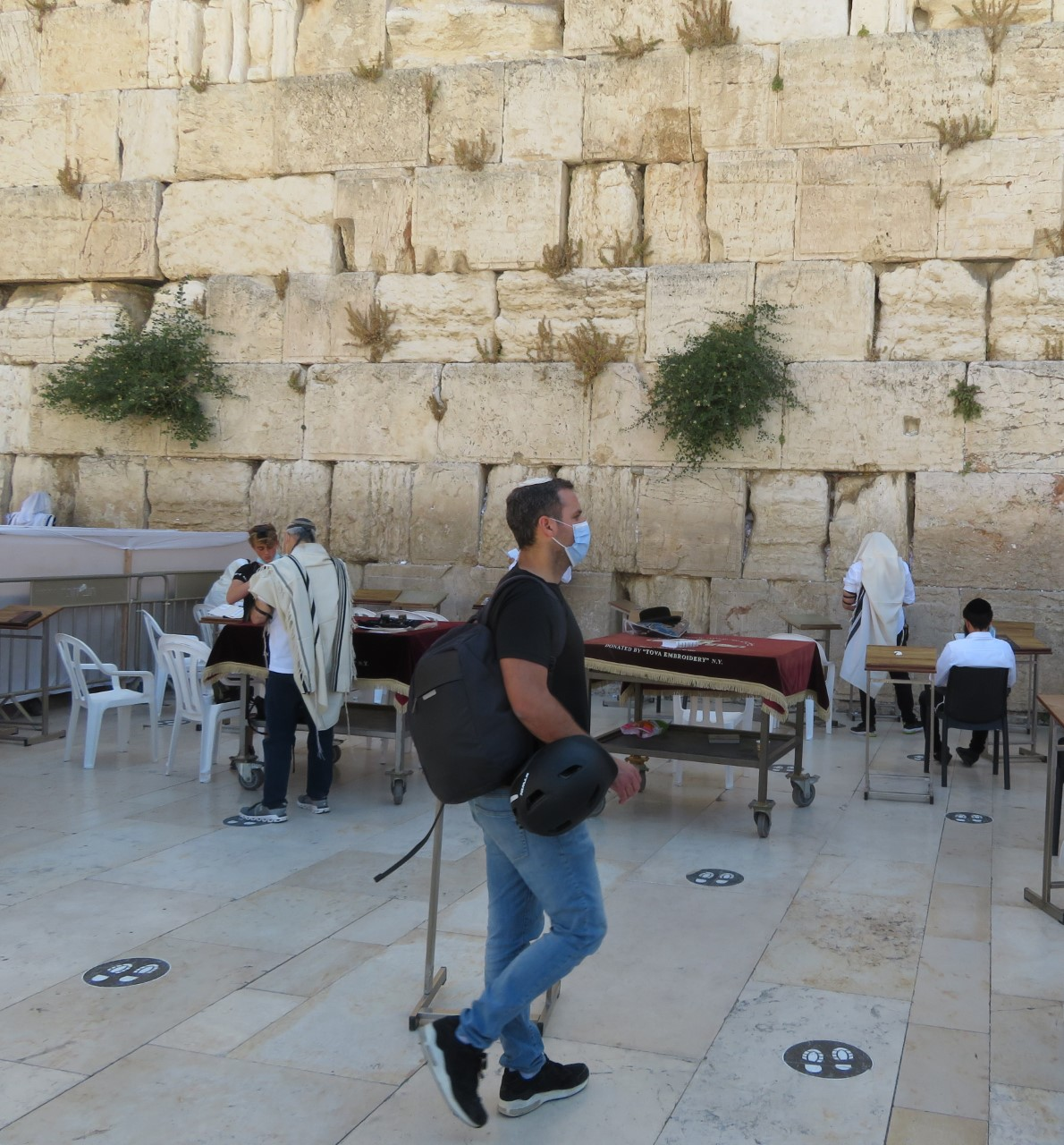 Practicing social distancing, an Israeli man waits his turn to pray at the Western Wall in Jerusalem.