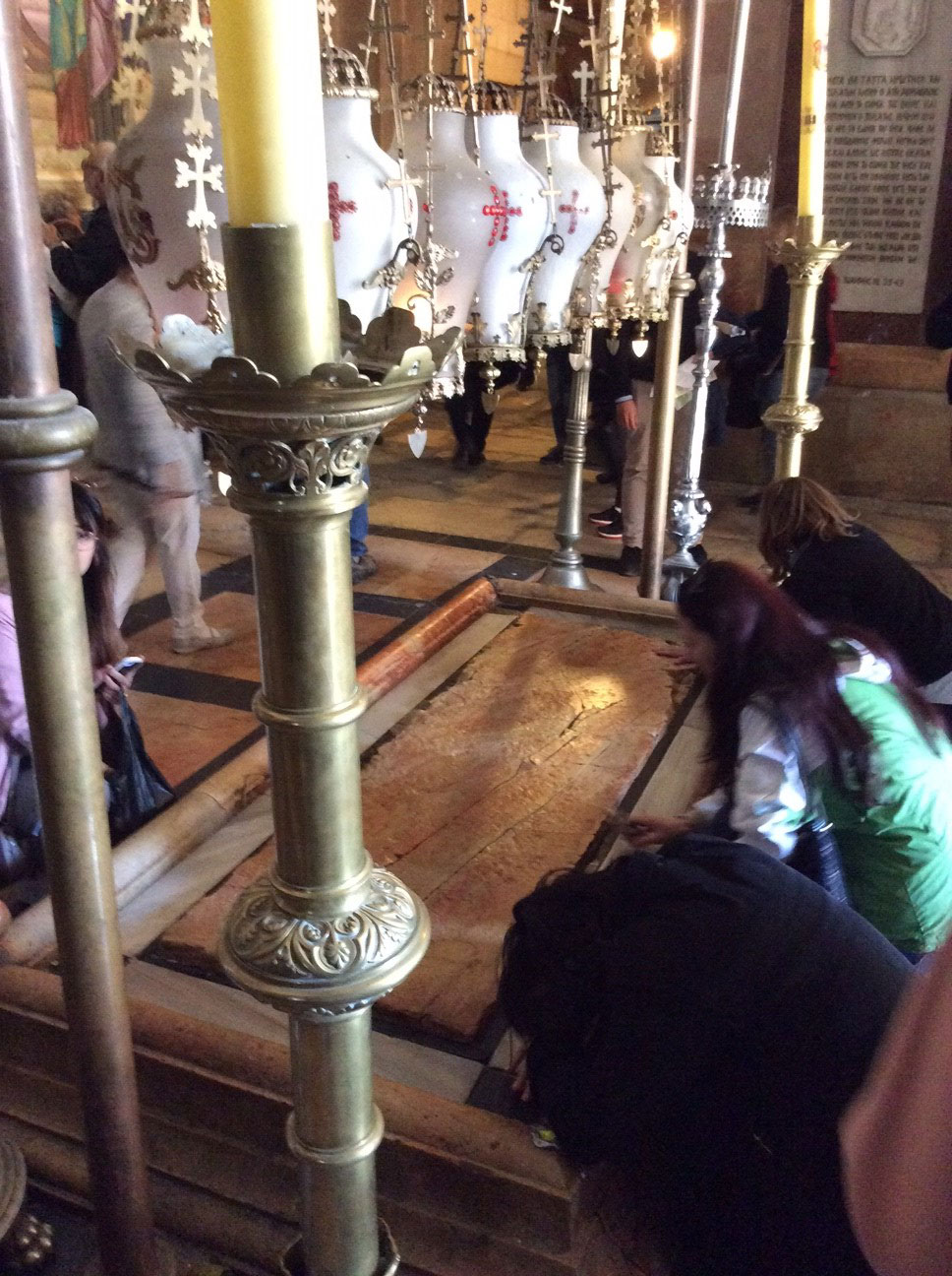 Pilgrims pray at the Stone of Unction, just inside of the Holy Sepulchre. Also known as the Stone of Anointing, it is the place where the body of Jesus was laid after being removed from the cross and prepared for burial by Joseph of Arimathea.