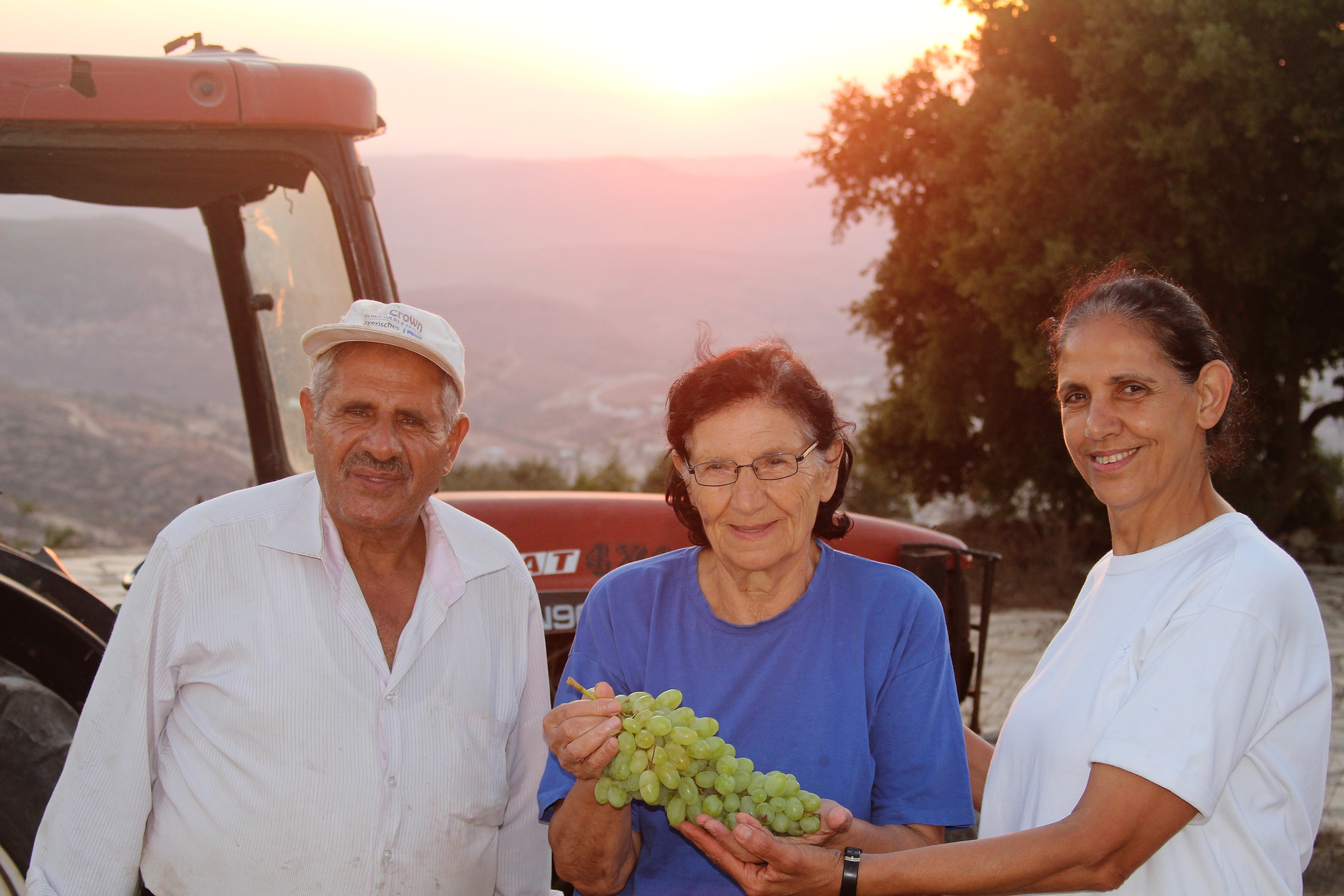 Daher Nassar (left) and his sister, Amal Nassar (right), with their mother, Miladi (center), displaying some of the farm's grape harvest. Photo: Rev. Kristen L. Brown