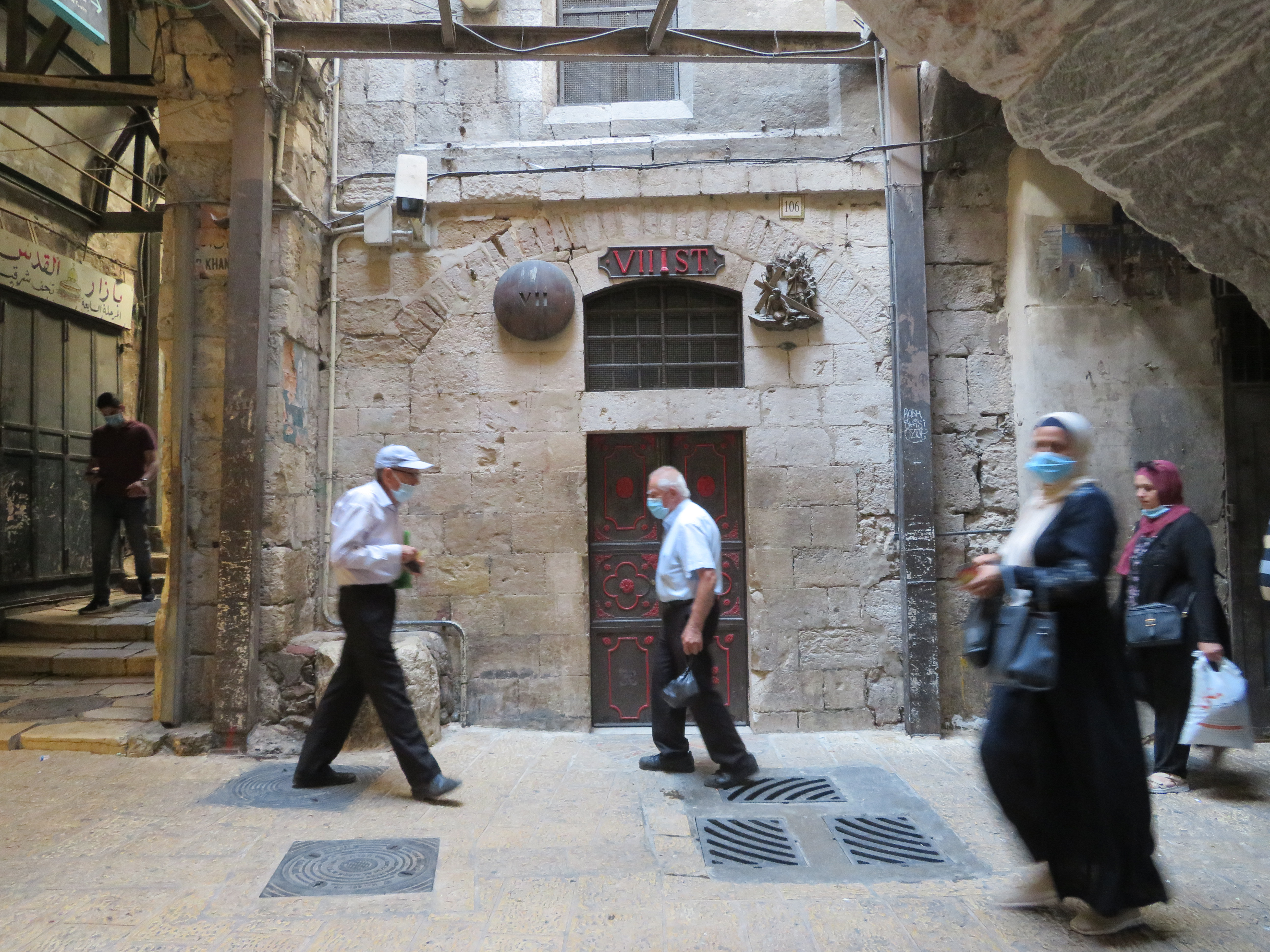 Masked shoppers in Jerusalem pass by the 7th Station of the Via Dolorosa, where tradition says Jesus fell for the second time.