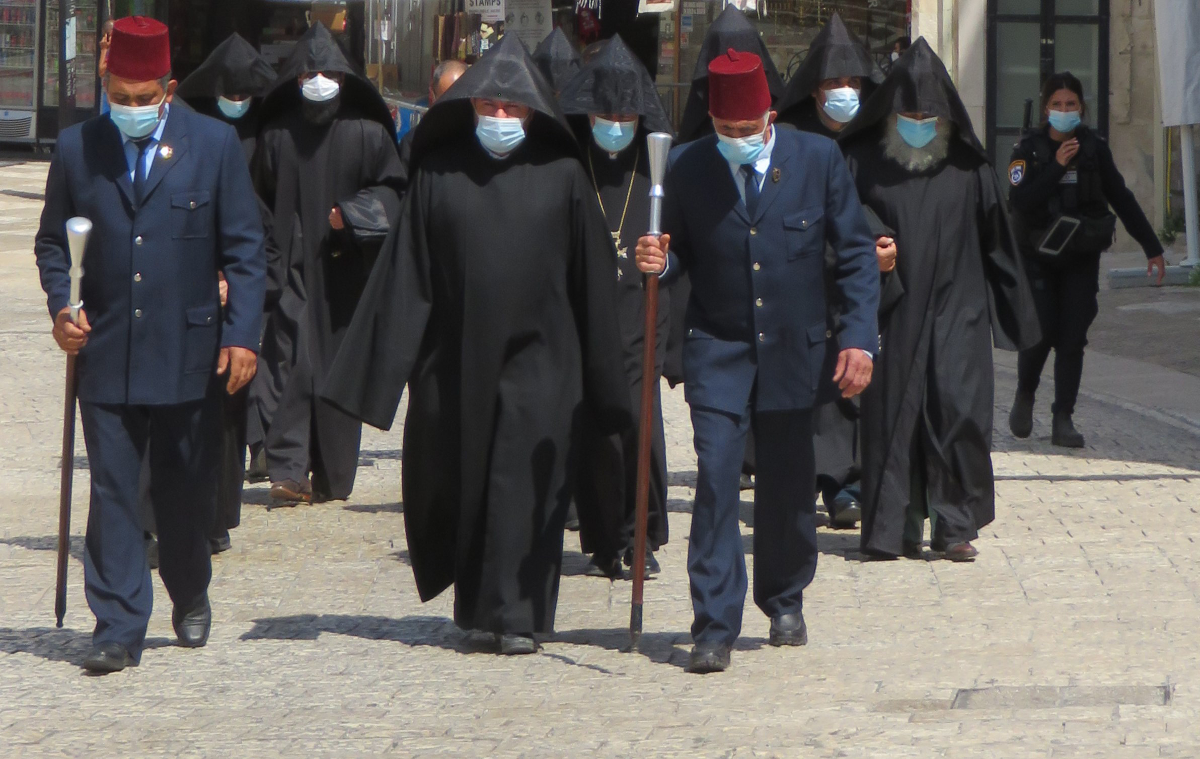 An Armenian Orthodox Procession, donning masks, makes its way through the Old City of Jerusalem.