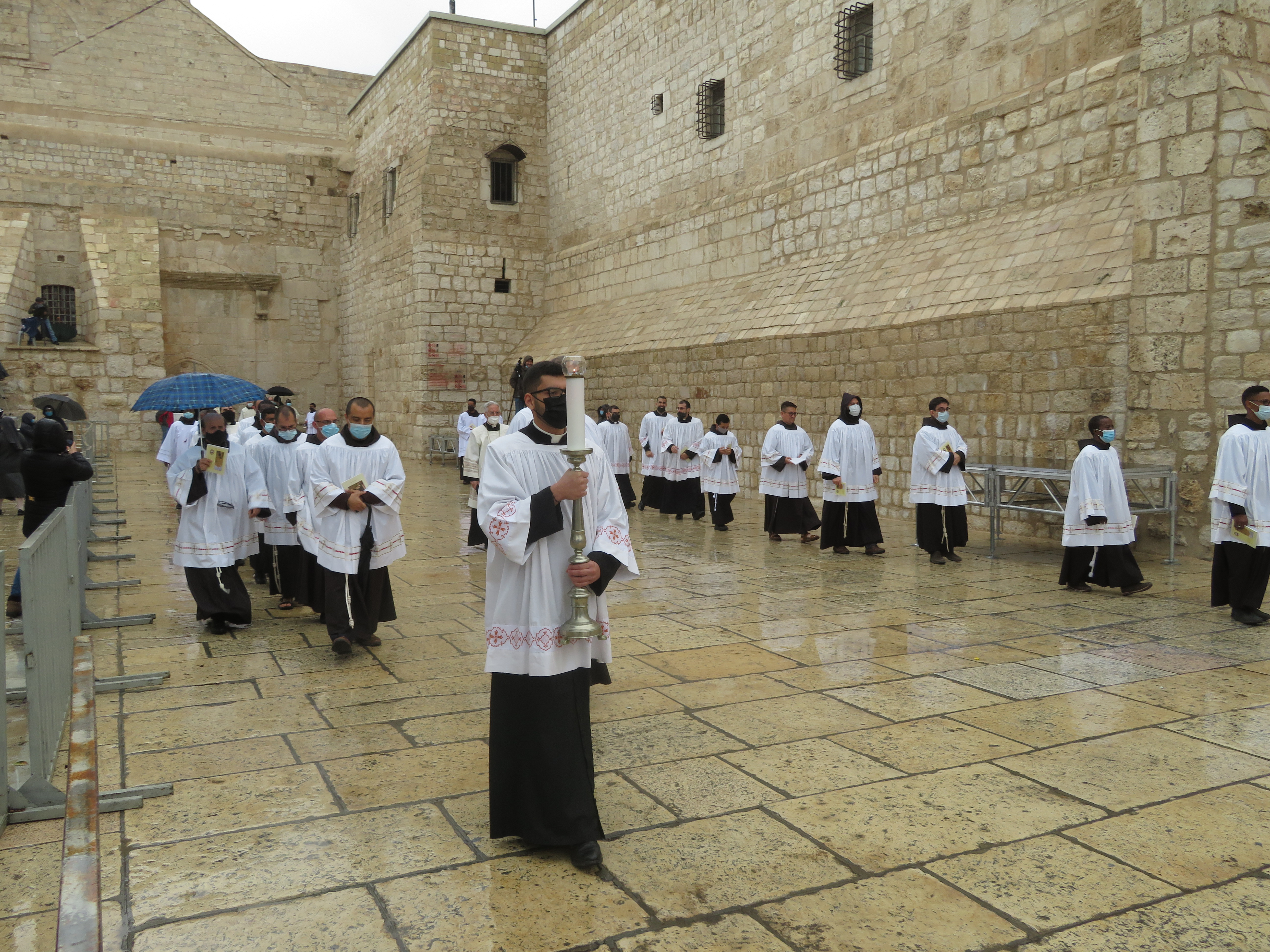 Processing during a pandemic:  Masked Franciscan priests process to Manger Square in Bethlehem on Christmas Eve, 2020.