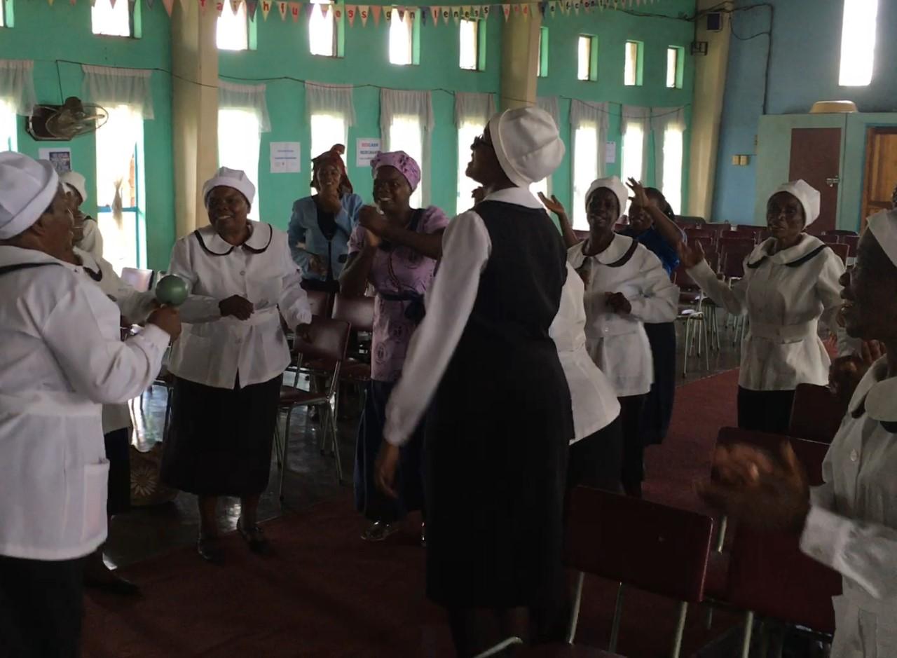Members of the Kuwadzana United Presbyterian Church Fellowship of Women worship joyously during their weekly meeting. (Photo credit Doug Tilton.)