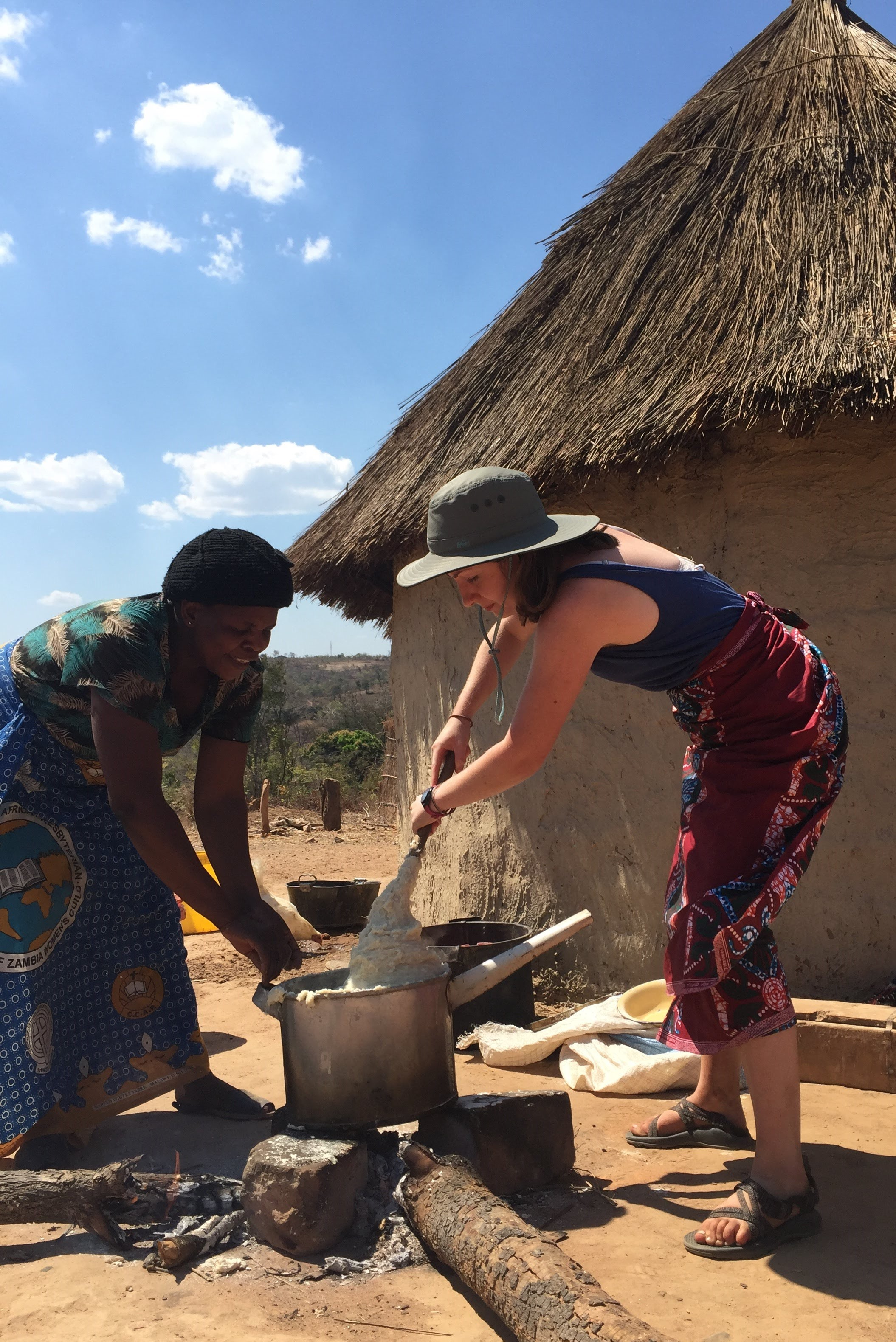 During in-country orientation, Zambia YAVs were hosted for a few nights in a village 90 kilometers outside Lusaka. Here Emily learns to make Zambia's staple food, nshima, over a fire, with cultural interpreter Mabuchi coaching and assisting.  Photo by Miguel Petrosky