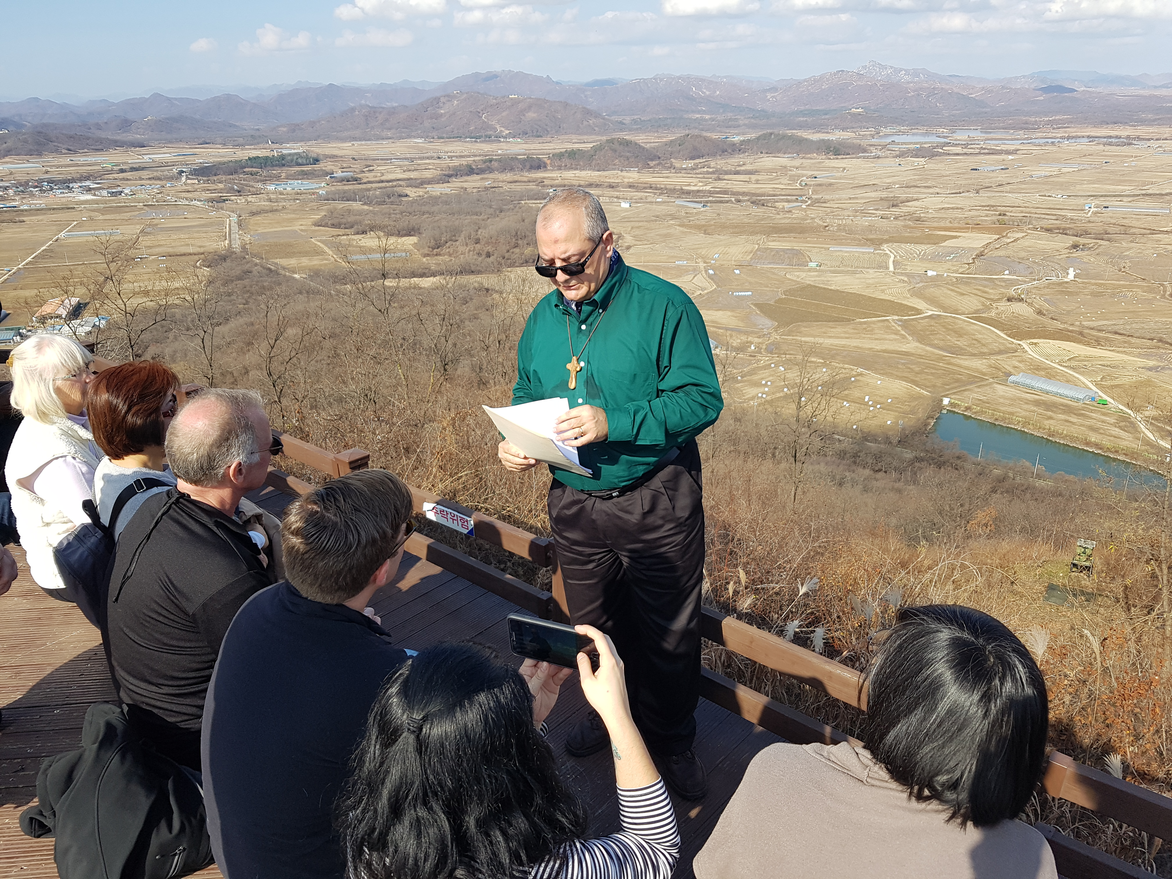 The Rev. Raafat Zaki leads a prayer at the top of Soi Mountain in South Korea at the DMZ border, with the mountains of North Korea visible behind him. (Photo by Kurt Esslinger)