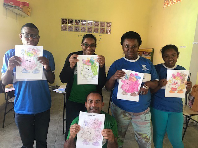 Young adults showing the pictures they colored in English class.