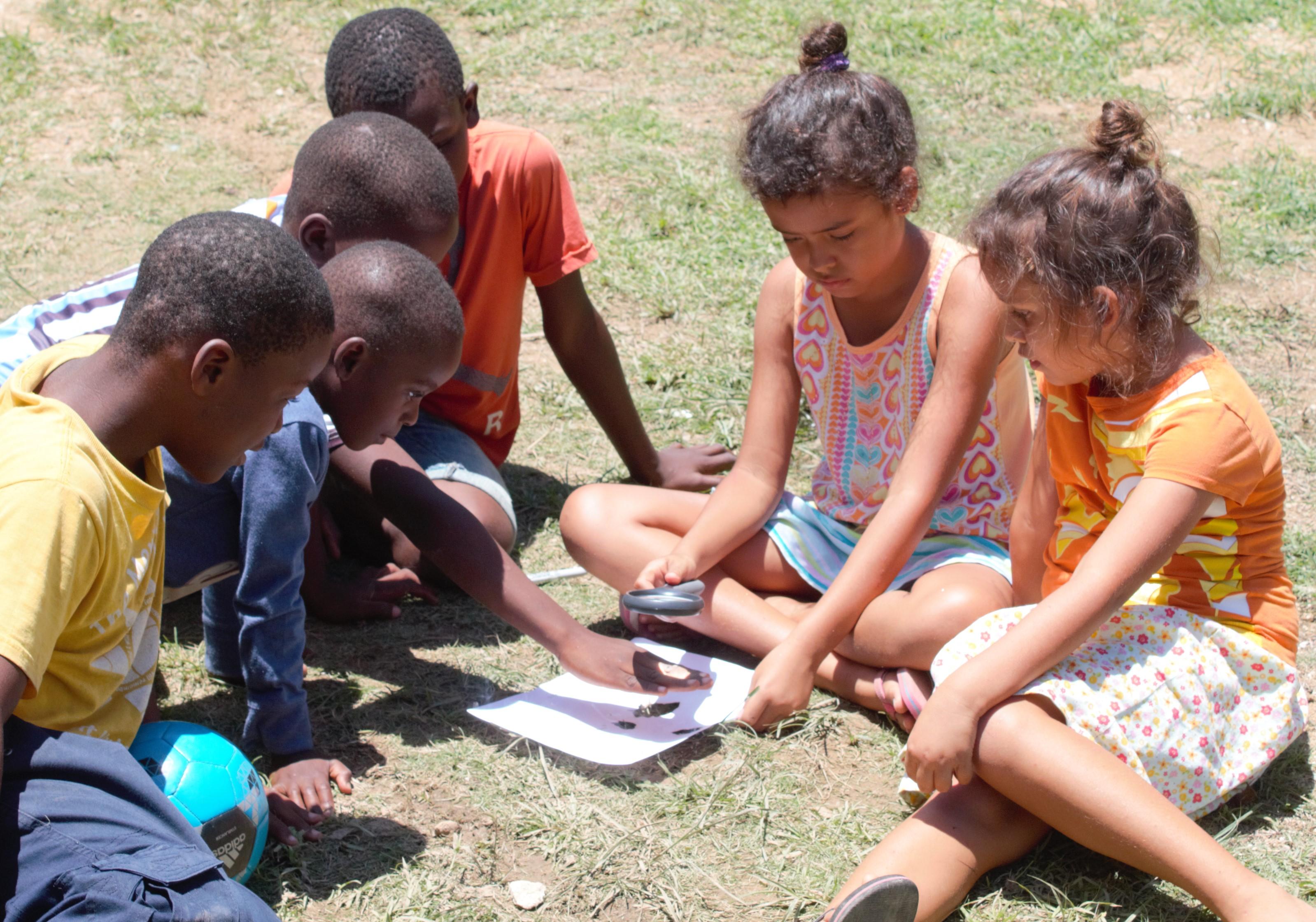 Keila, Annika y algunos niños cerca del centro de formación en Mombin Crochu juntos aprendiendo a concentrar la energía solar para quemar papel.