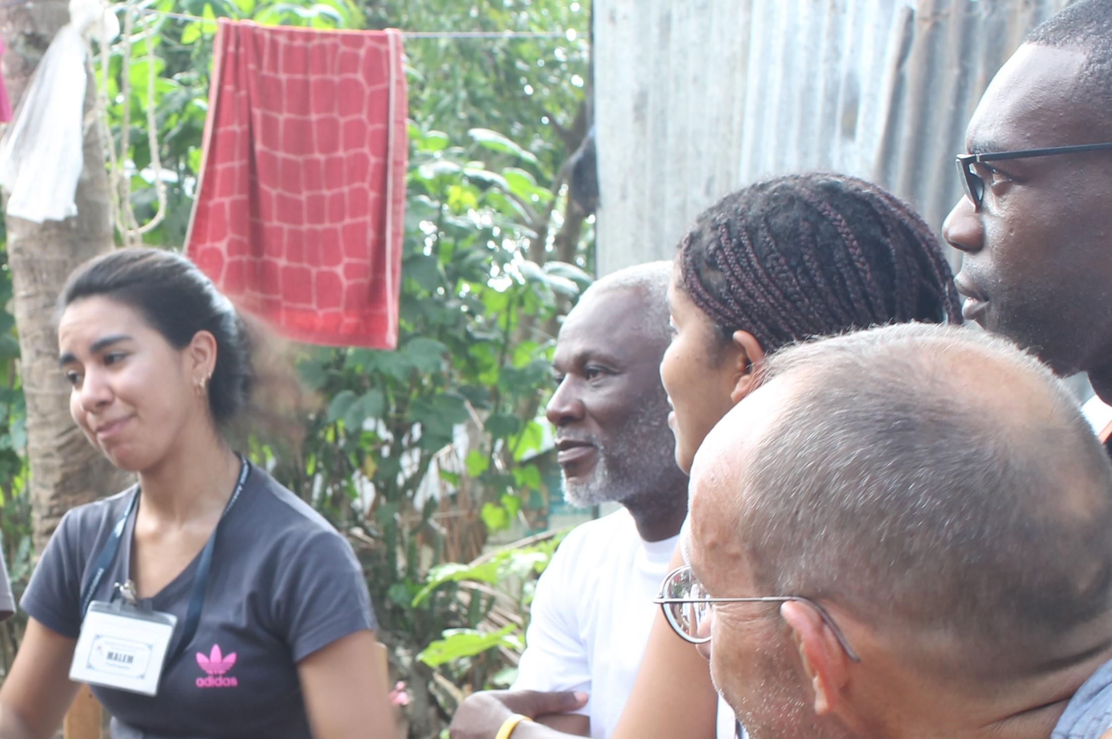 Juan Batista (extremo derecho, detrás de la cabeza de Marcos) y Bellanira Matos (a la izquierda de Juan) ven a una compañera estudiante de Chile (izquierda) llevar a cabo una lección de salud con un grupo de niños que forman parte del Club infantil ECS en Mombin Crochu. Nuestro anfitrión y director del programa de ECS en Haití, Osse Saint-Juste, se encuentra entre Bellanira y la estudiante chilena de ECS.