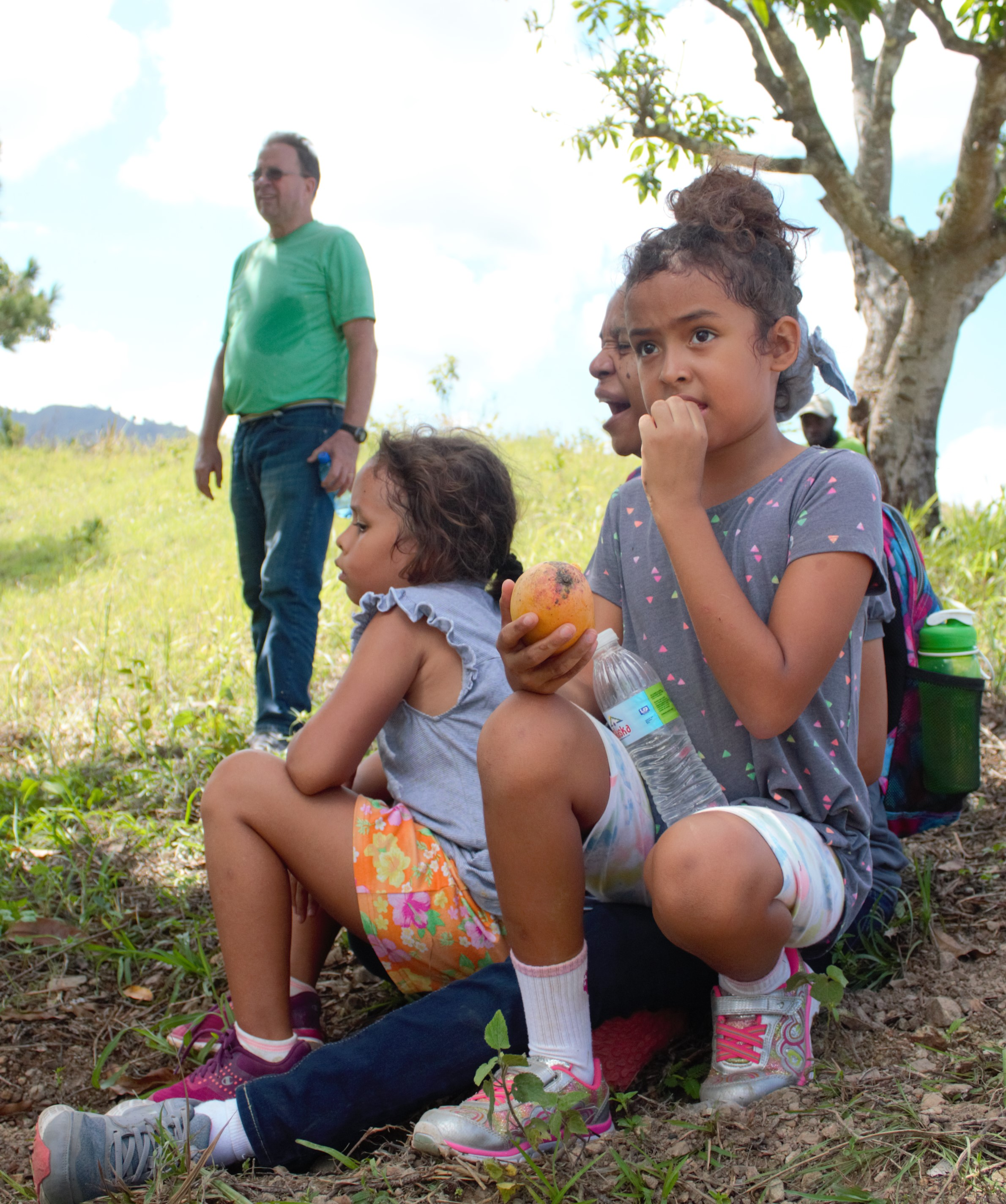 Keila and Annika taking a break with Jenny on the walk to visit the community of Mapou in the mountains of north-central Haiti. The mango in Keila's hand may have come from the tree to the far right.