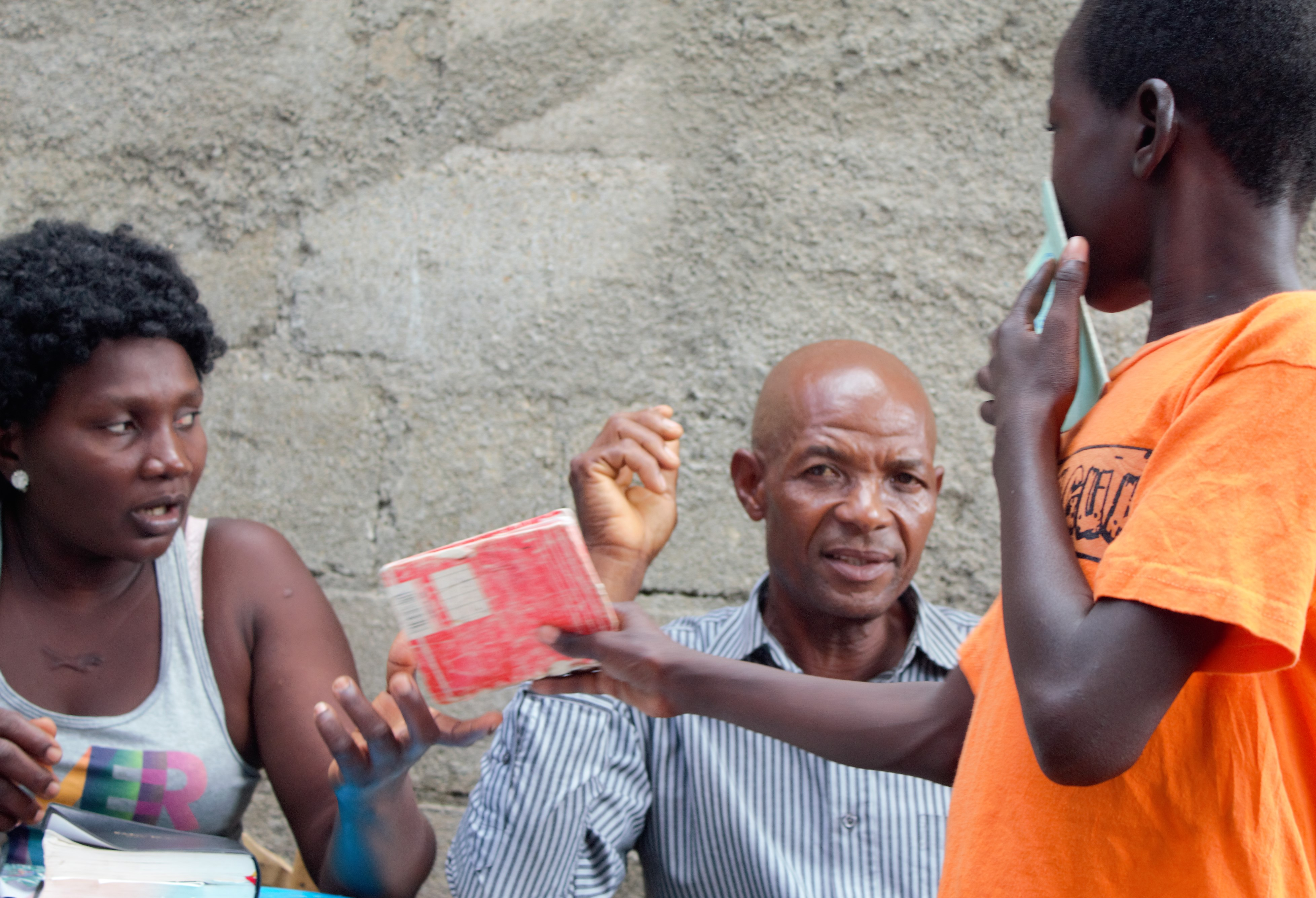 "A young boy from Mombin Crochu getting his savings card signed after he deposits between 25 and 50 gourdes (between $0.30 and $0.60) in the savings ""safe"" locked with three padlocks. The respective keys are given to three different adults. Everything each child saves over one year is returned at the beginning of the school year, plus some interest that is earned from lending money to adults from the children's families."