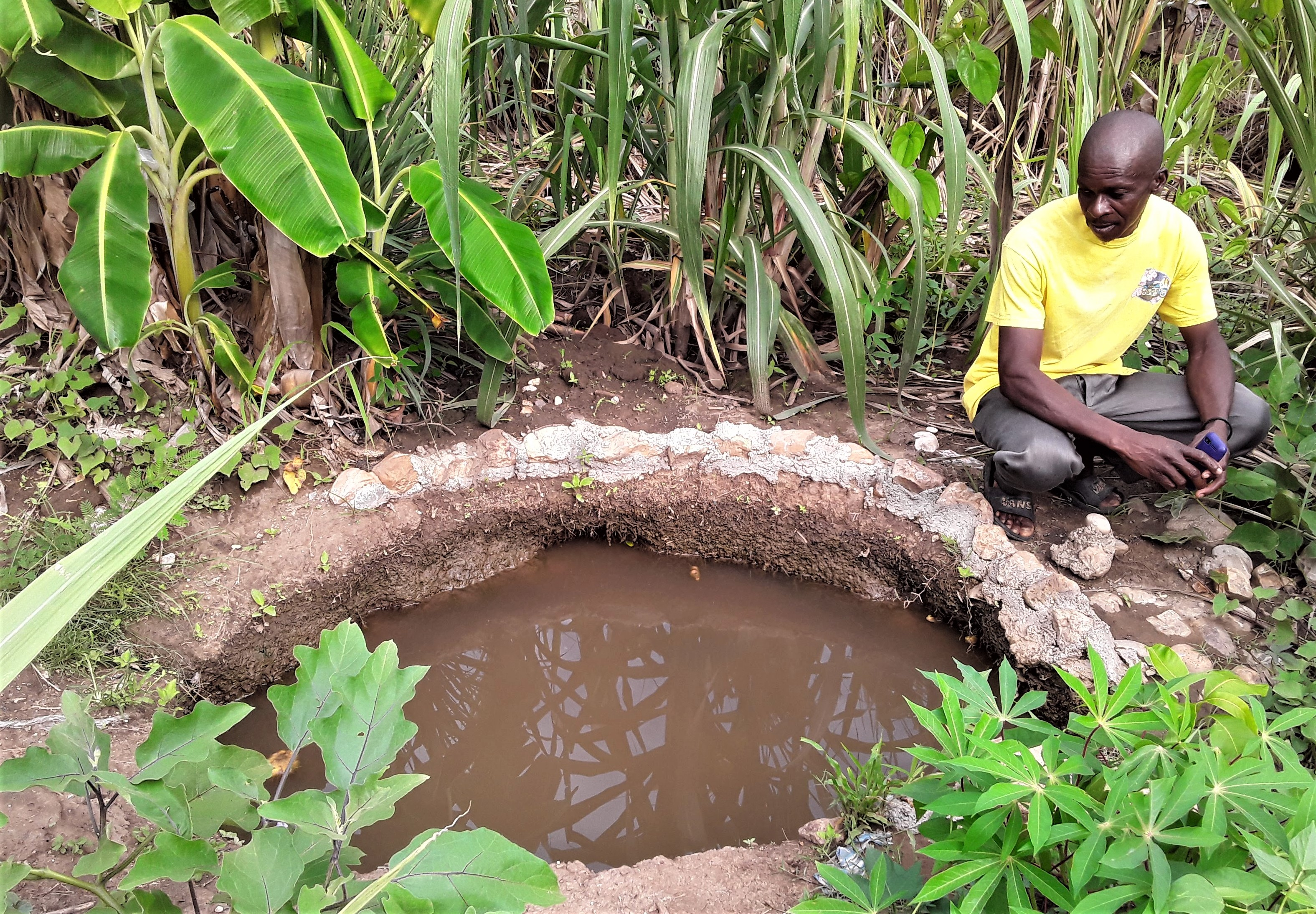 Eco-village resident from Village 3 showing Eric, Herve and me his fish pond in the middle of his vegetable garden plot by his house.