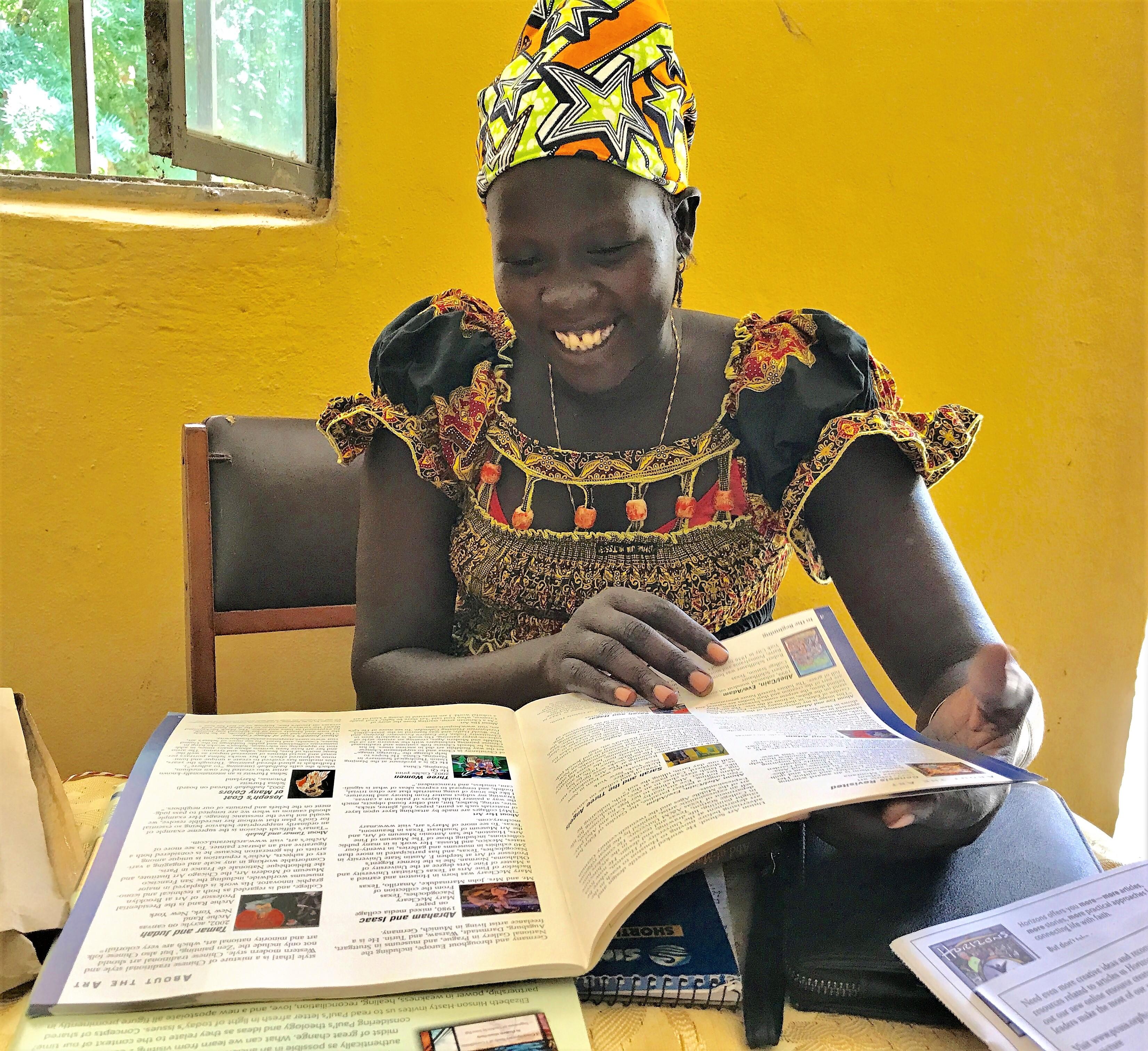 "Nyadak Gatwech Tut, Women's Desk Western Gambella Bethel Synod, looking over ""Horizons Magazine."""