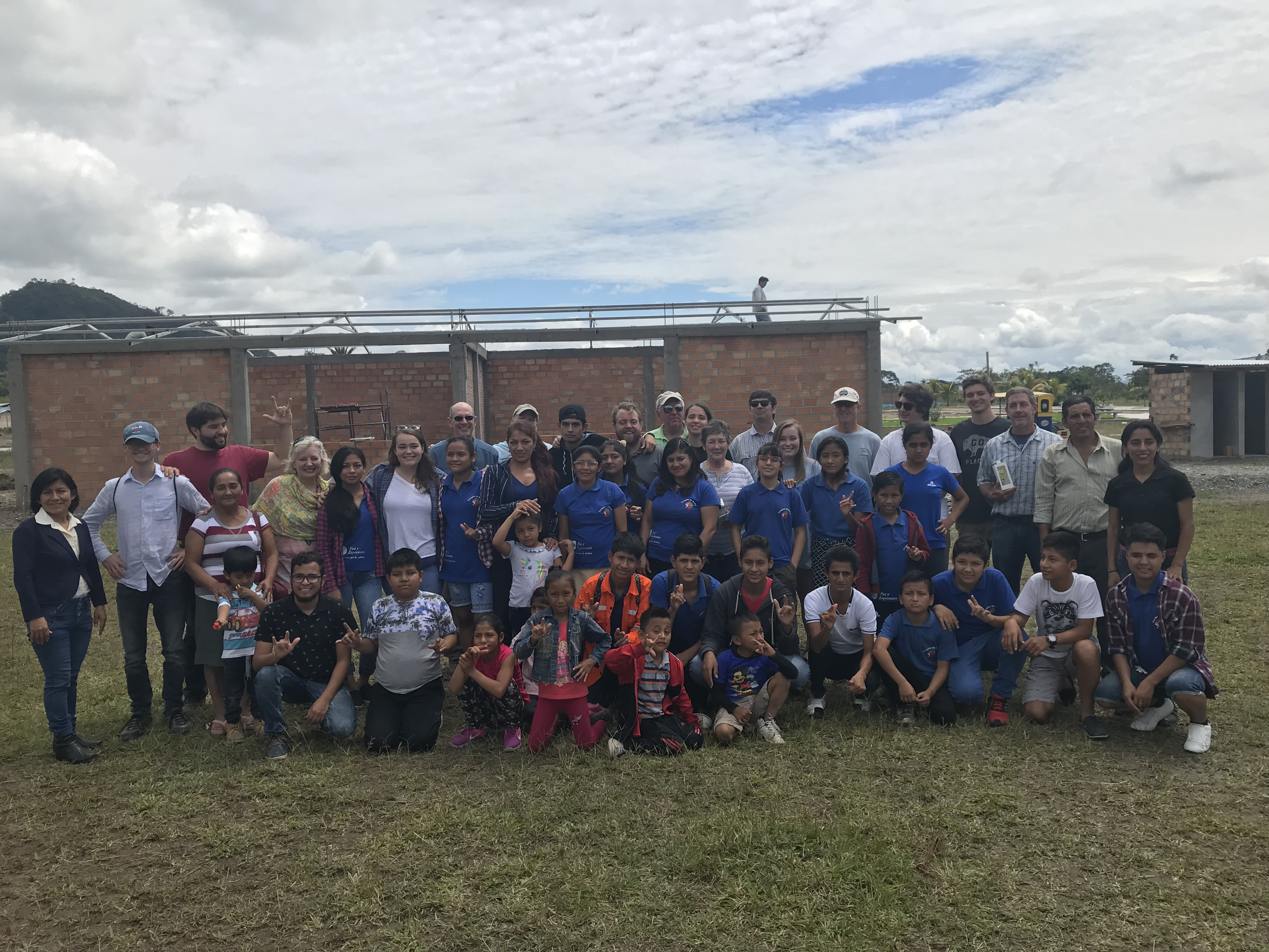 The mission team from Brownson Memorial Presbyterian Church (Southern Pines, NC) stand together with students and parents in front of the nearly finished school in August.
