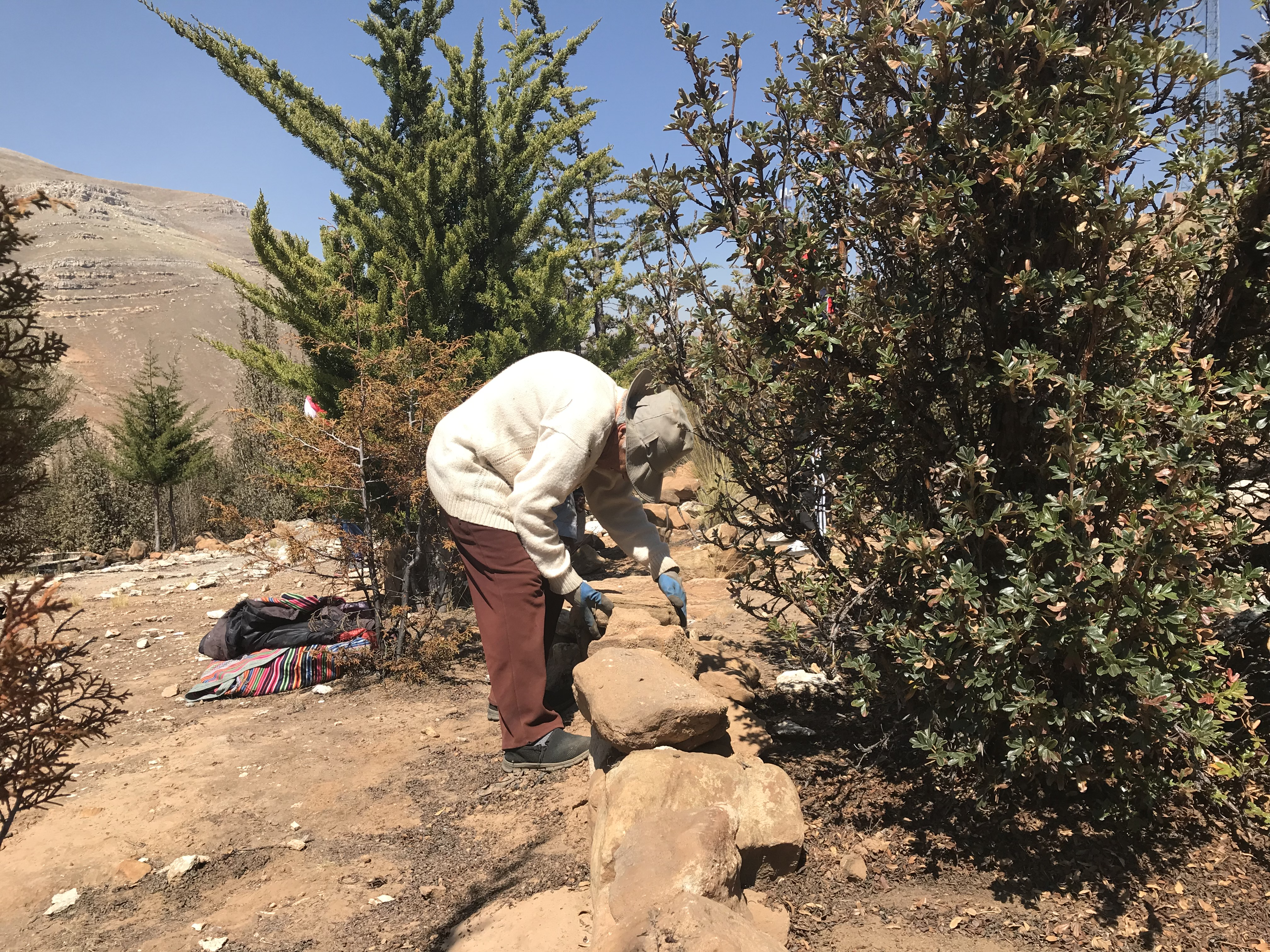 Mama Toya labors away at building rock walls for the terraces.