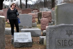 Sally Amon discovers the toppled gravestone of her grandmother Anna Ida Hutkin at Chesed Shel Emeth Cemetery in University City on Feb. 21, 2017. (Photo courtesy of Robert Cohen/St. Louis Post-Dispatch)