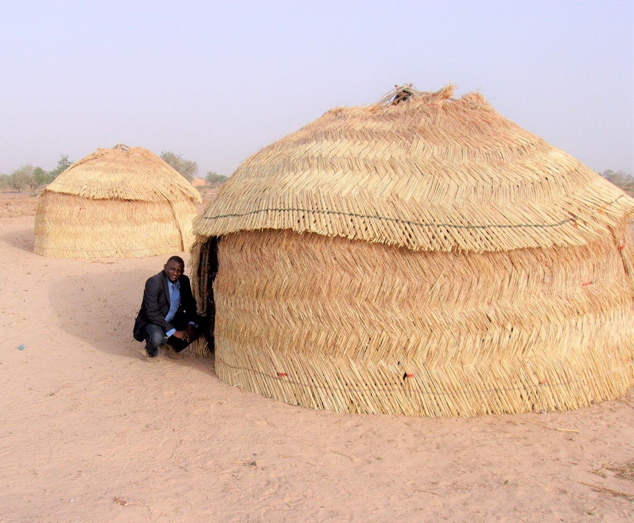 Mr. Ayouba Jadi of the EERN WASH Section finding shade by two classrooms of the newly formed Bible College in Mailo, about 4 hours east of Niamey.