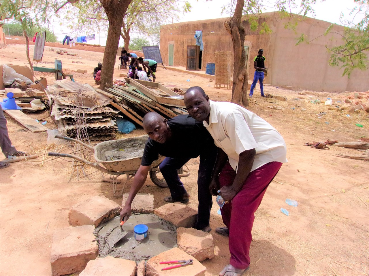 Two of the Community Health Evangelists (CHE) learning to build a child's latrine slab.