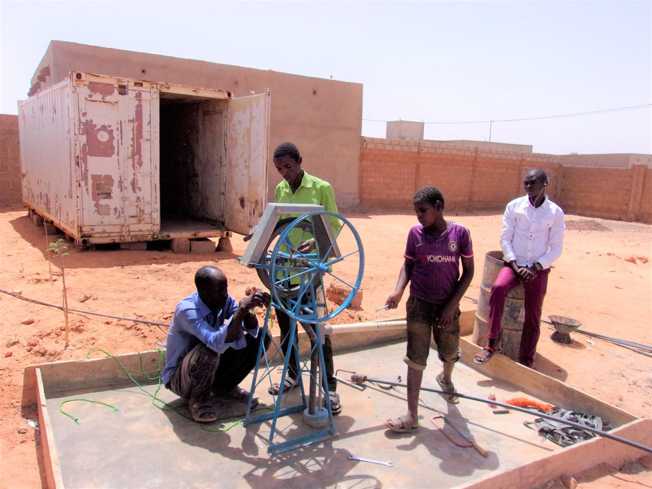 M. Chafaghane (left), master fabricator of rope pumps and manual drilling tools installing a rope pump at the Niamey SMART Centre which is being established.