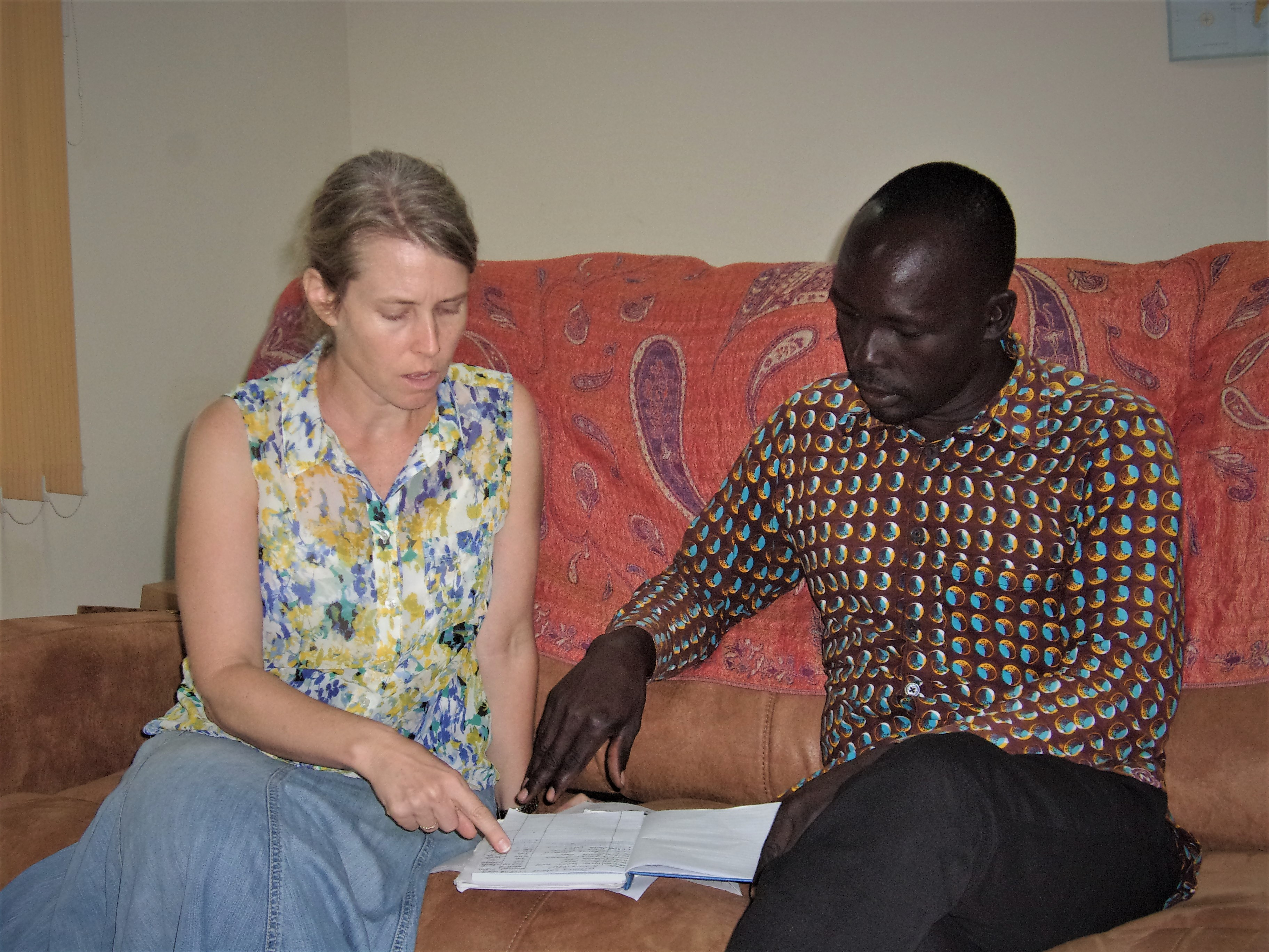 Kristi Rice working with Mr. Okoti to establish a bookkeeping system that is relevant to him.