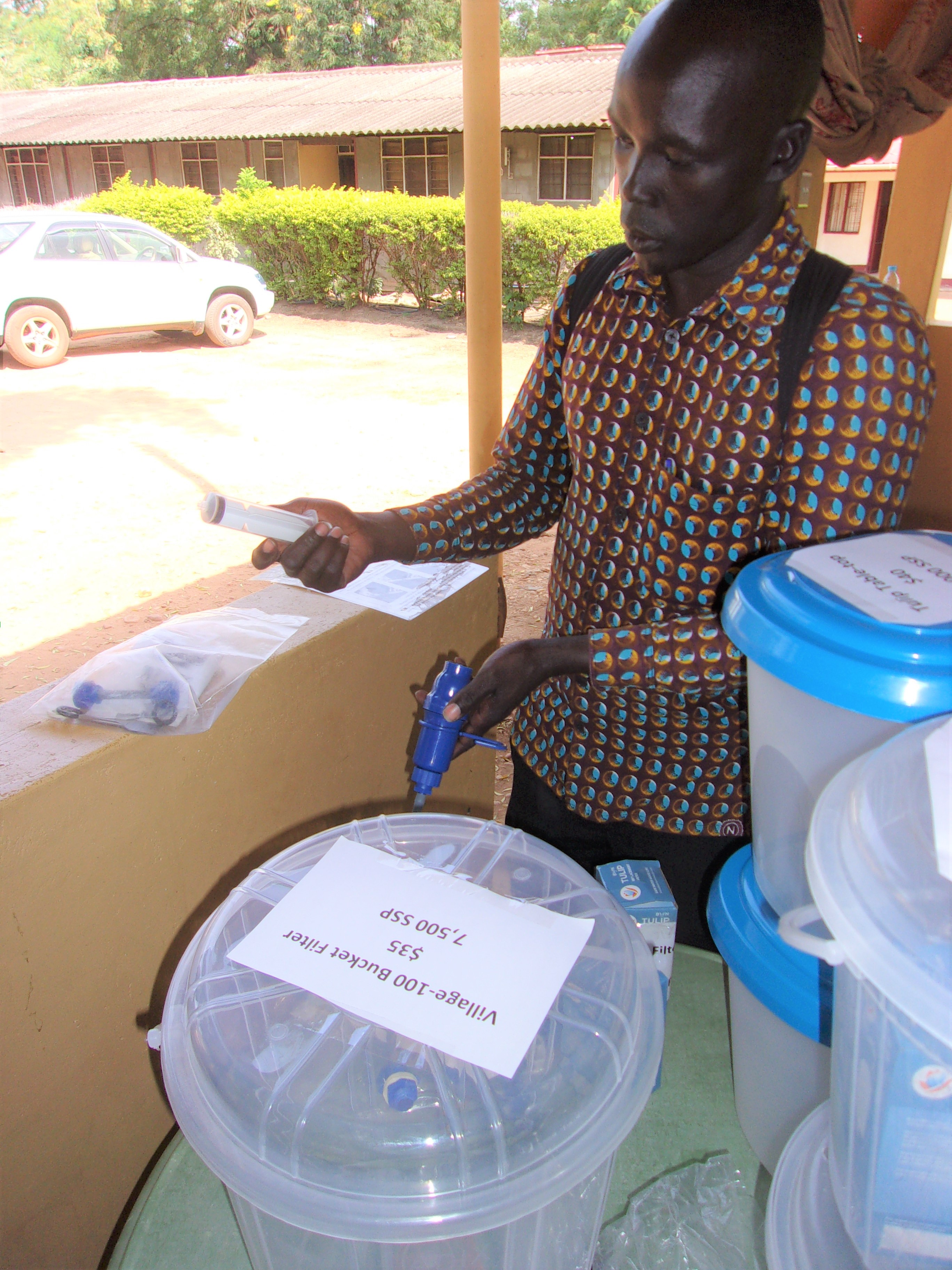 Mr. Okoti with water filter bucket systems for sale.