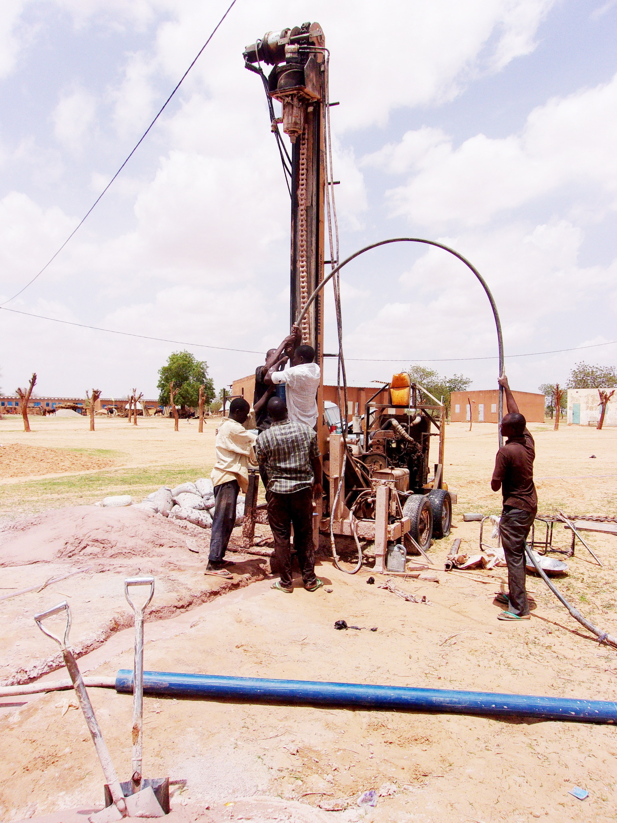 The drilling team pumping water into the well to flush out the mud at the Bible College.