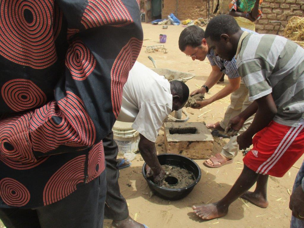 """Michael Ludwig and his colleague Pastor Issa showing the evangelist how to make a wood-conserving """"rocket stove."""""""