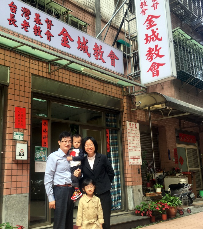 Pastor Hen Rong and her husband, Dong Ming, stand with their two children in front        of Jin Chen Church.