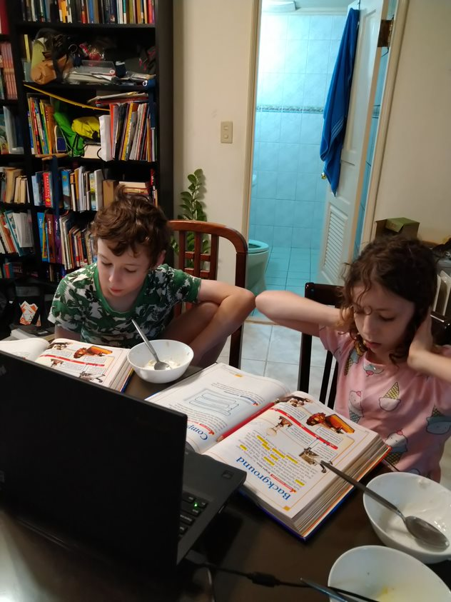 Eli and Eva do some online reading with grandparents.