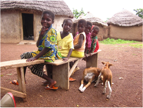 Children from a Christian family in northern Ghana, who are members of an ethnic group that has traditionally been Muslim, sitting outside the family compound with their dogs.