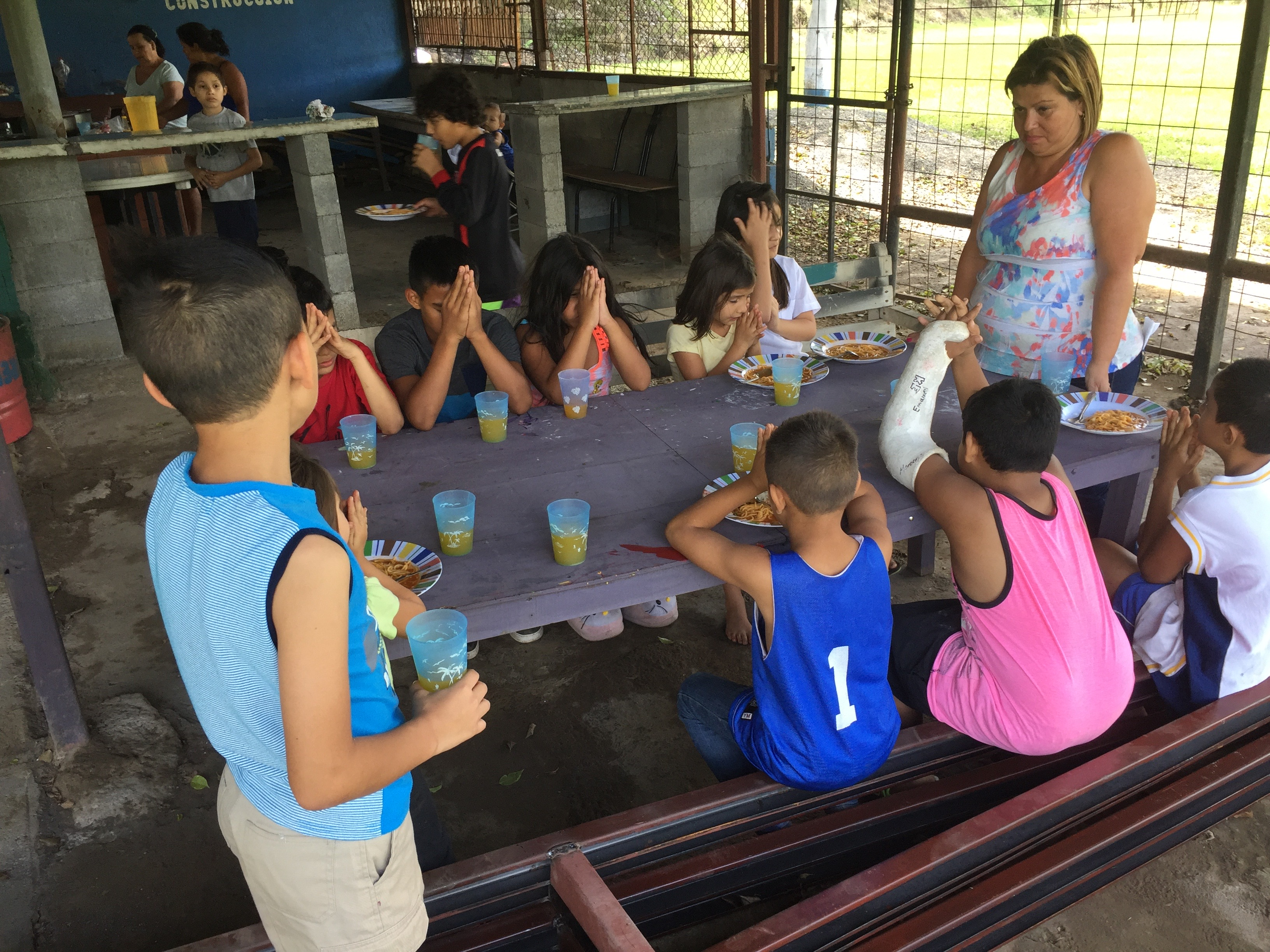 Children praying before their meal at one of the children feeding program service sites of the Evangelical Presbyterian Church of Costa Rica.