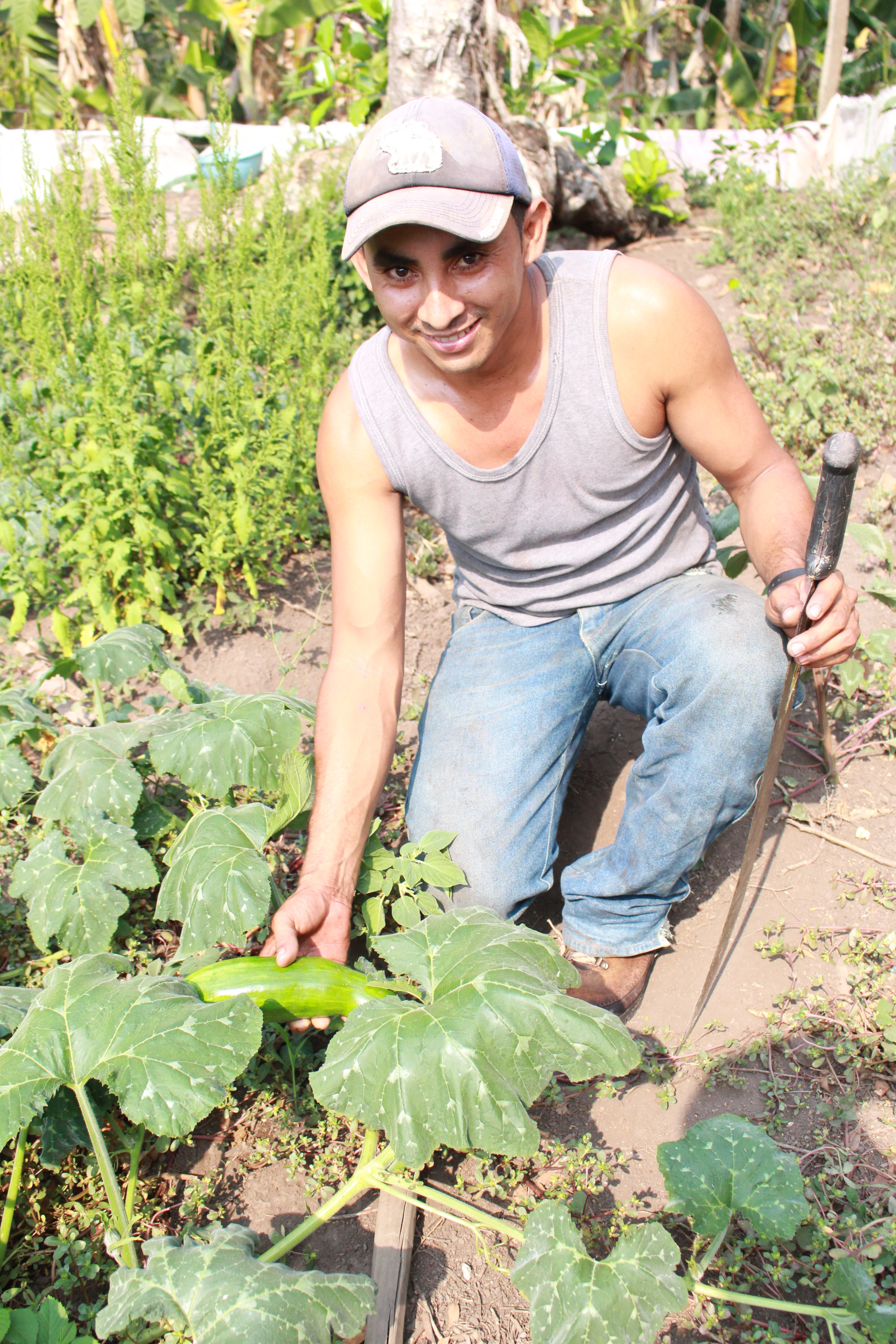 Yorbin shows off a growing squash, amid a variety of vegetables that will help better nourish and sustain his family.