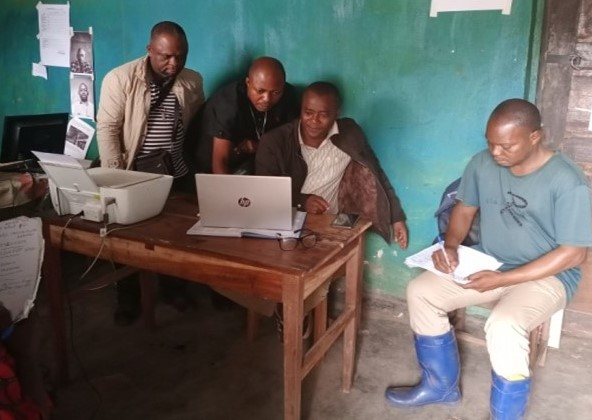 Bwanamusuri and the supervision team take a look at nutrition data at the  Ferenkeni health zone office.